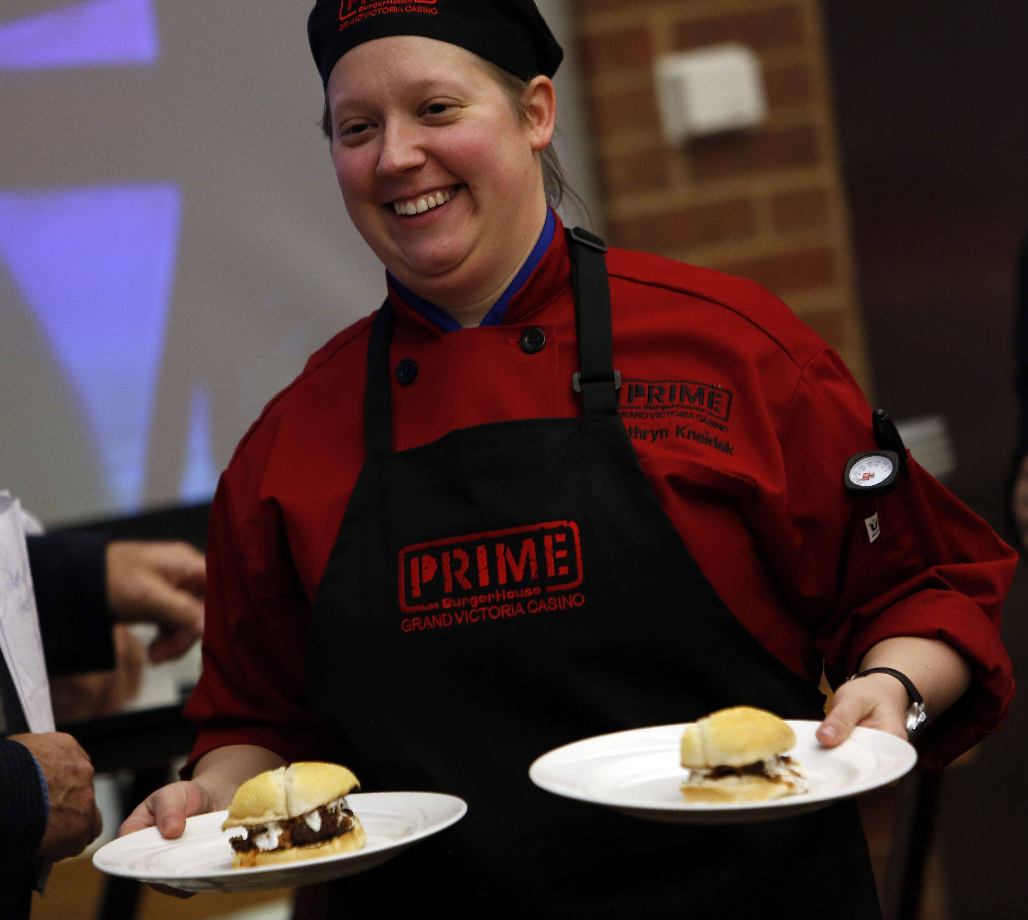 Kathryn Kneidek of Hanover Park delivers her South of the Border Chili Cheeseburger to the judges at Elgin Community College's fifth annual ECC-Prime BurgerHouse Burger Competition Friday at the Spartan Terrace Restaurant in Elgin.
