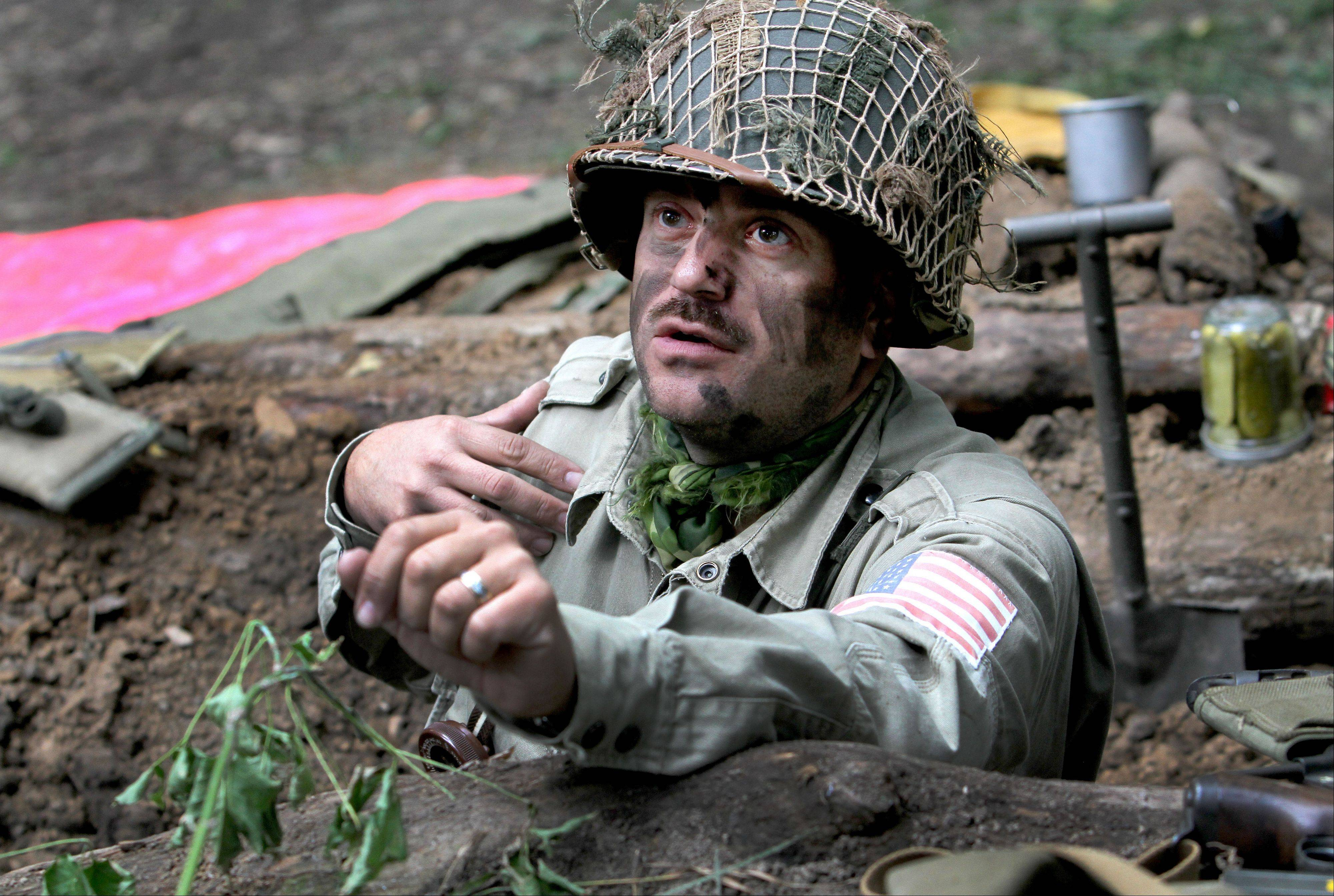 Re-enactor Steve Zahareas of Schaumburg looks out from a foxhole that he helped dig out, at World War II Days in Rockford.