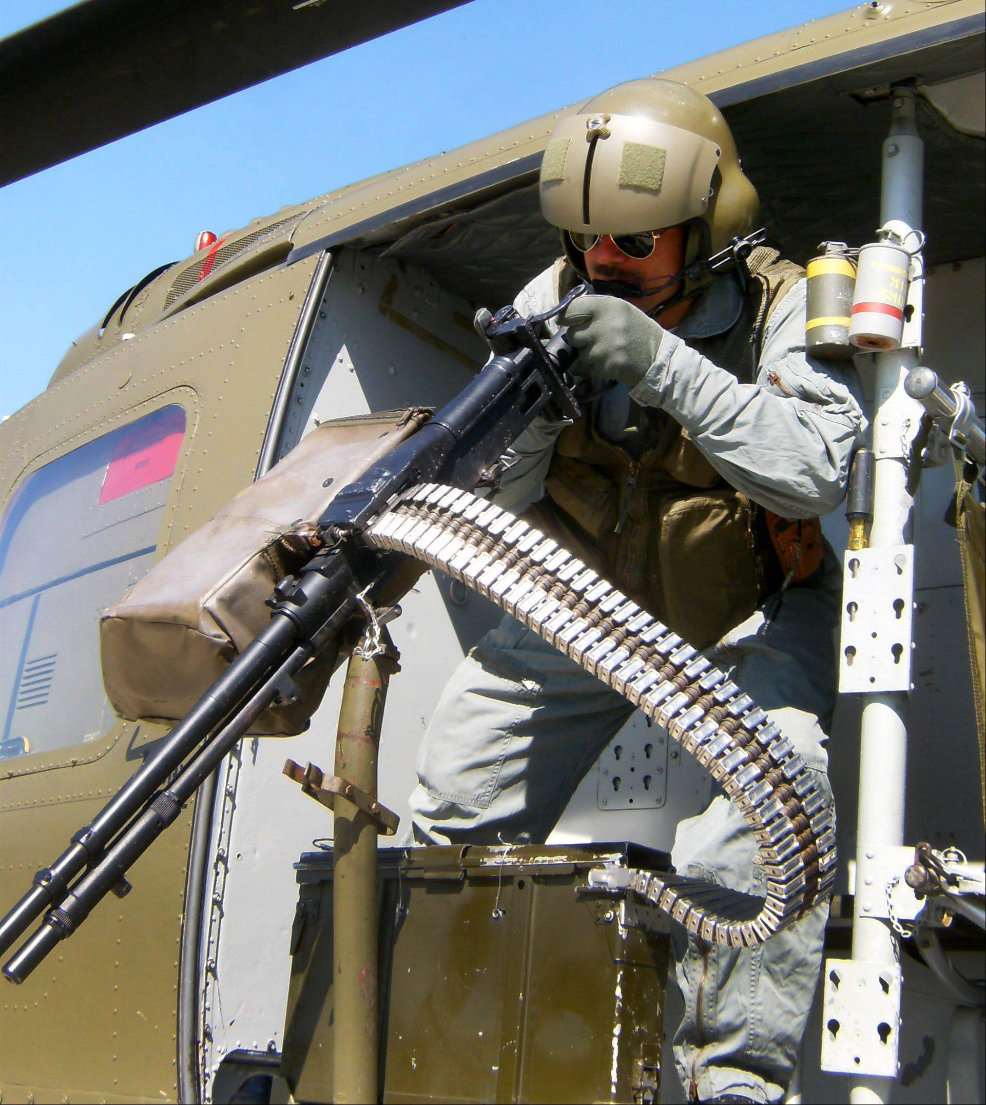 Steve Zahareas portrays a door gunner on a Huey helicopter UH1 during a Vietnam War re-enactment.