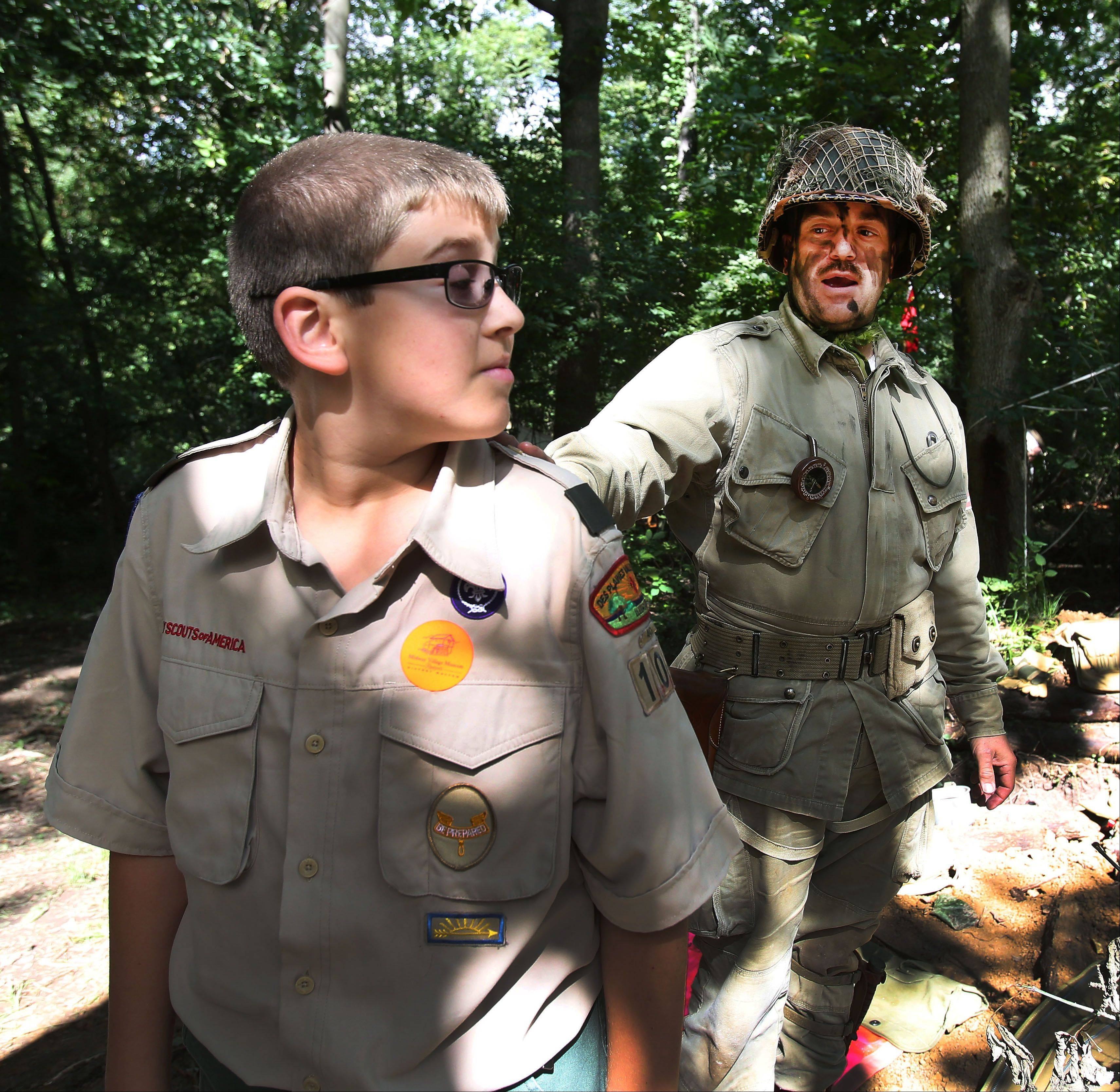 Cole Haubenreiser, 12, of Darien, gets a lesson in fighting a World War II battle from Zahareas during World War II Days in Rockford.