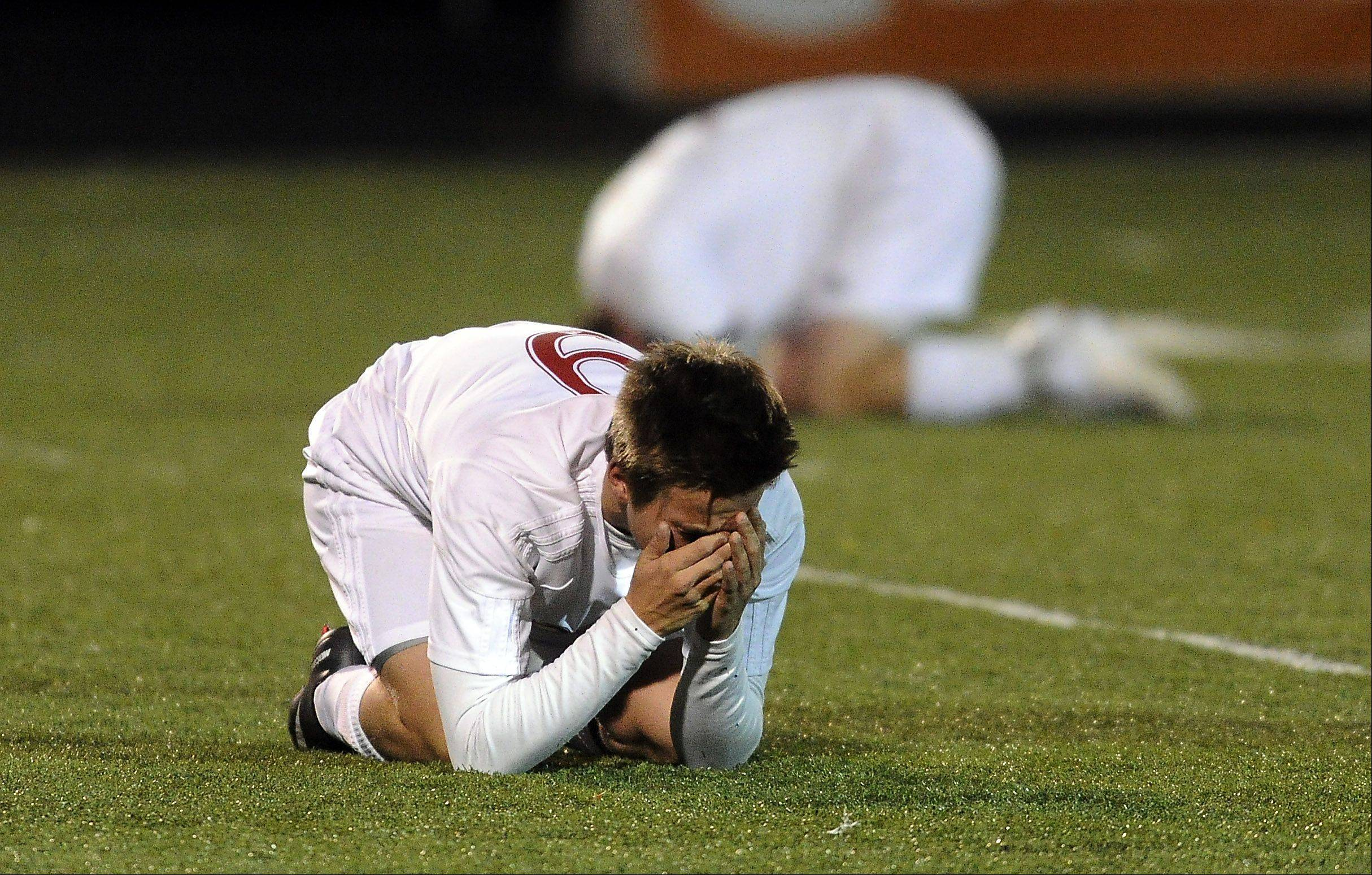 Naperville Central's Jordi Heeneman covers his emotions in the 3-1 loss to Edwardsville's in the Class 3A state semifinals at Hoffman Estates High School on Friday.