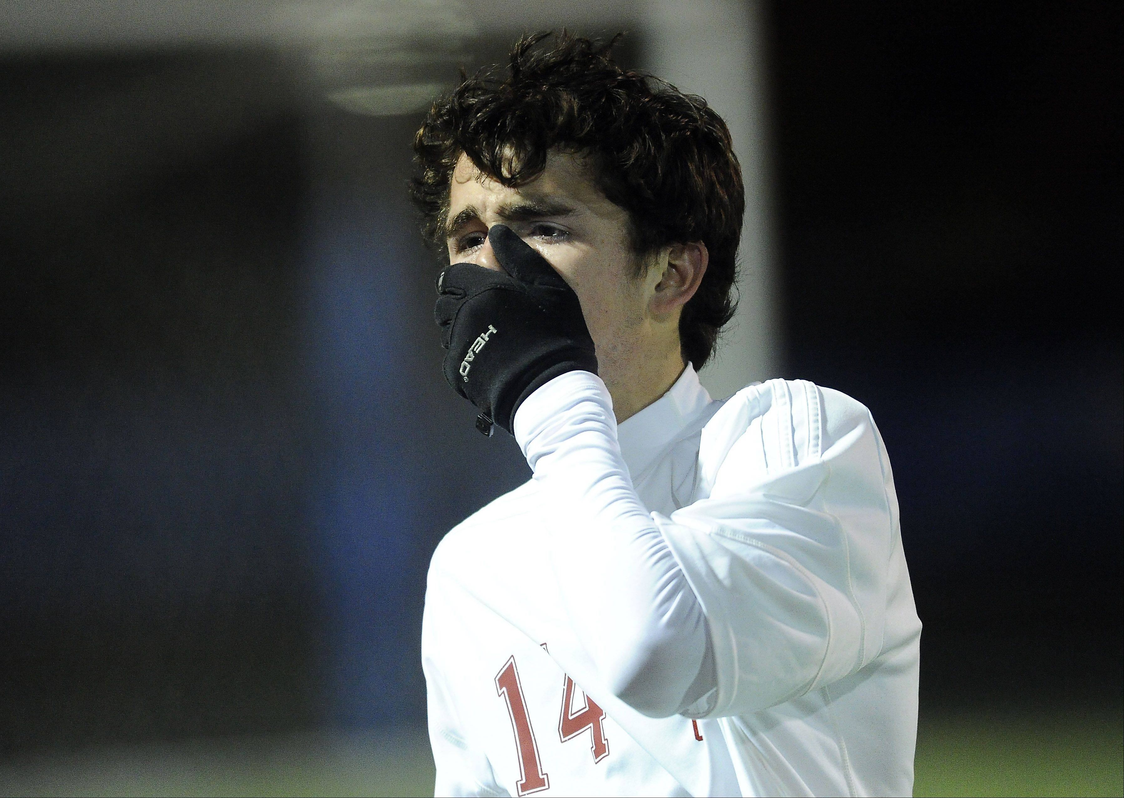 Naperville Central's David Murphy covers his emotions as he walks off the field in the 3-1 loss to Edwardsville's in the Class 3A state semifinals at Hoffman Estates High School on Friday.