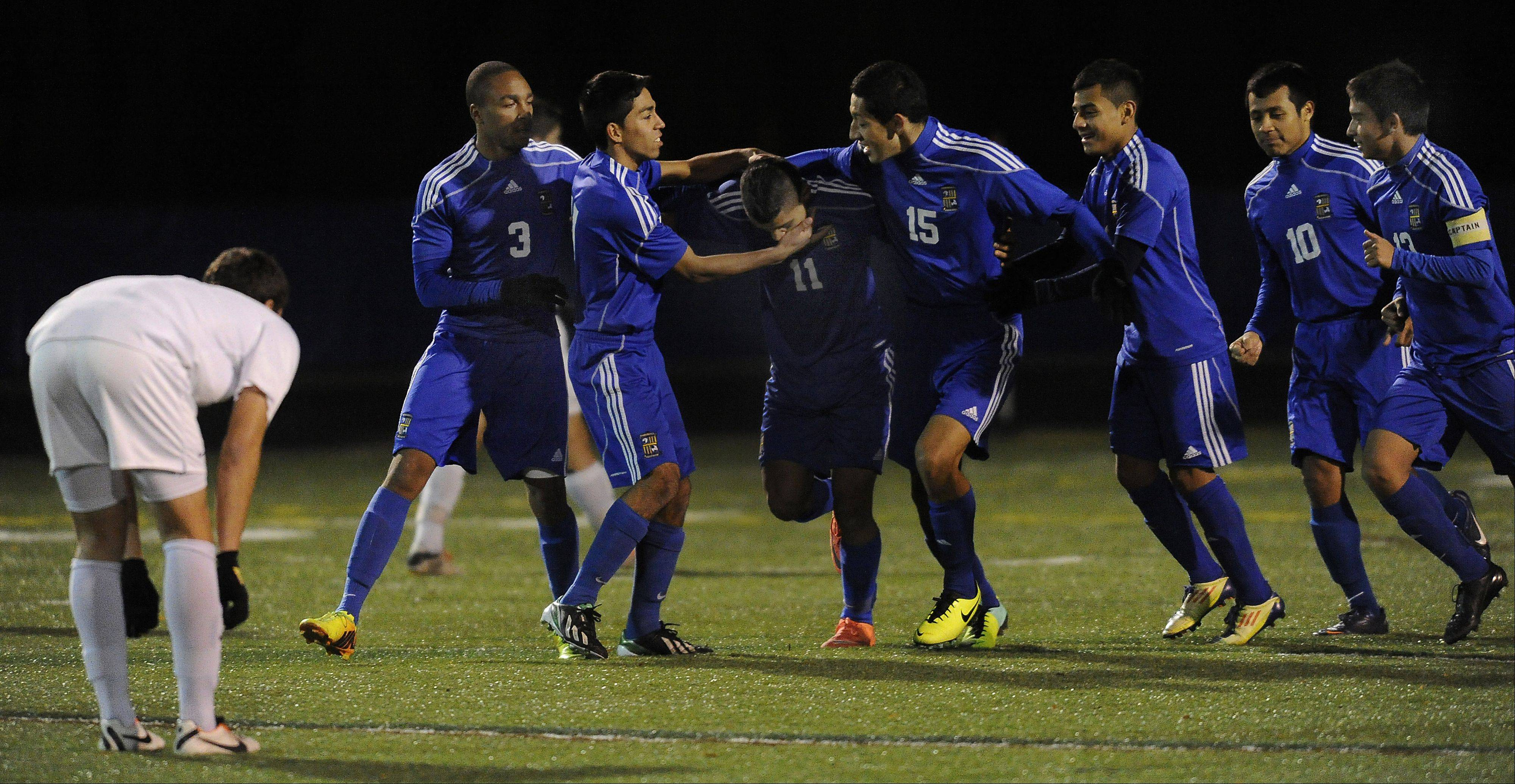 Wheeling's Luis Herrera, middle, scores the first goal as his teammates swarm him in the first period in the Class 3A boys soccer state semifinals at Hoffman Estates on Friday.