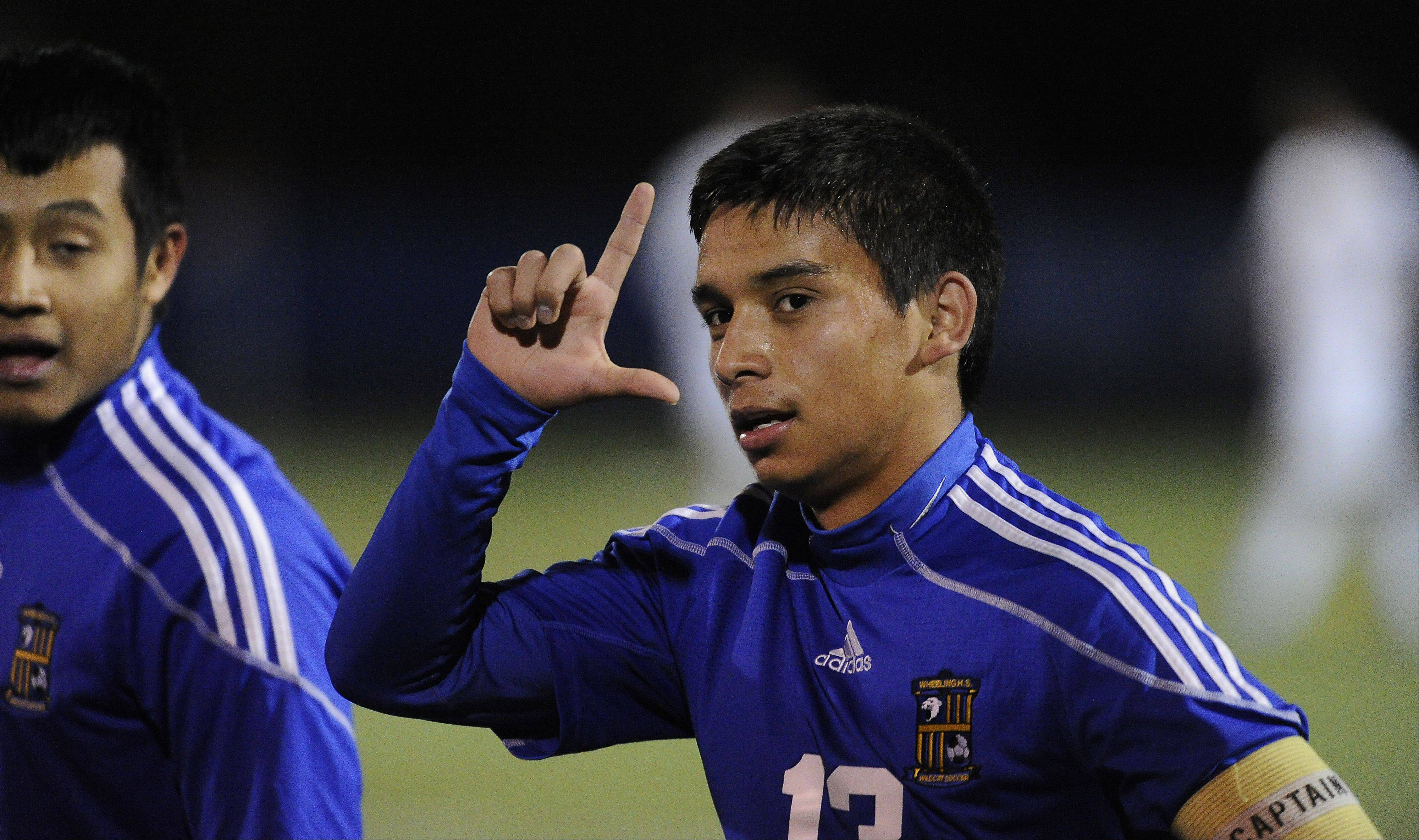 Wheeling's Jose Garcia scores the second goal as he looks to fans in the first period of the Class 3A boys soccer state semifinals at Hoffman Estates on Friday.