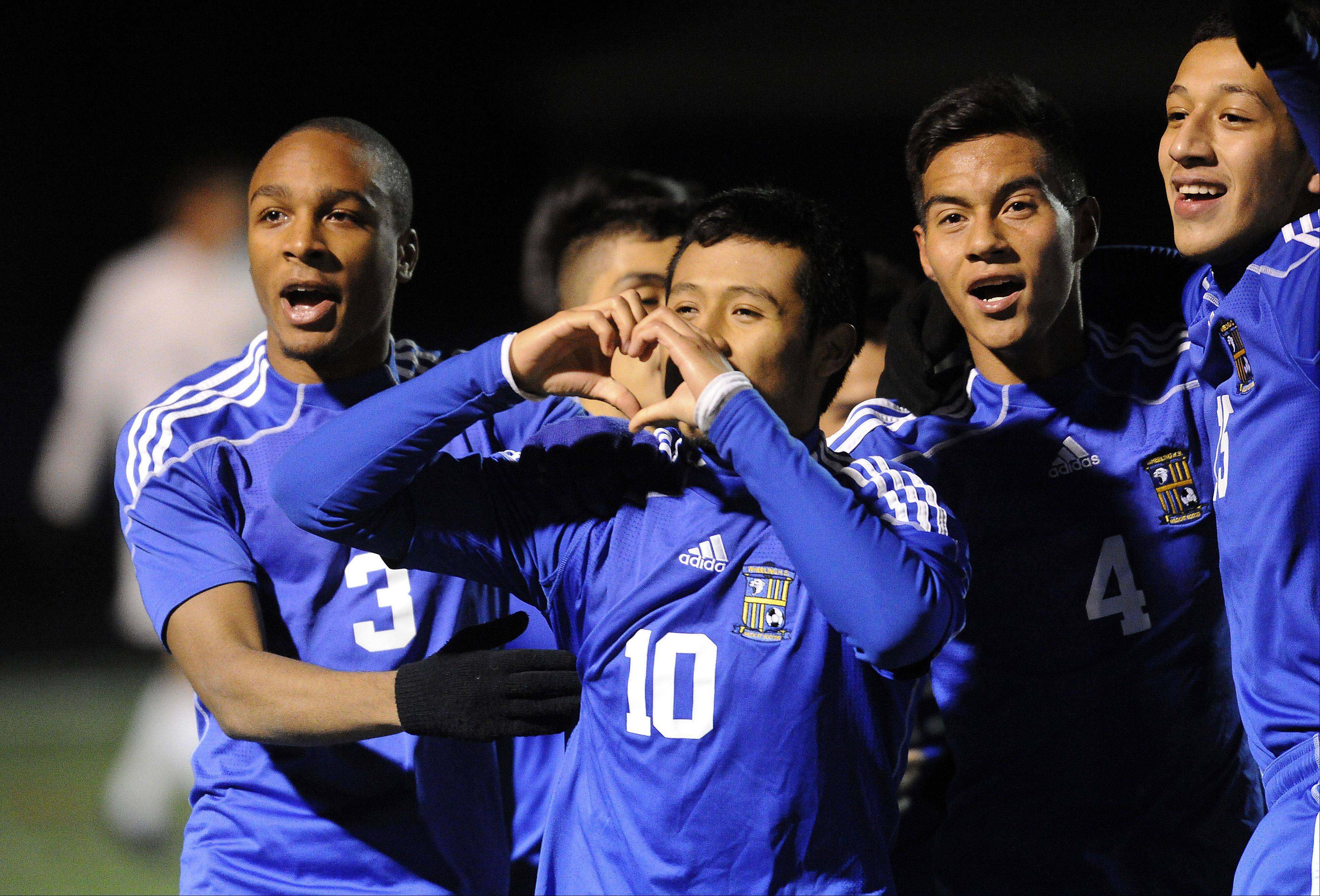 Wheeling's Ivan Manicilla shows some love for the Wildcats' fans after his goal in the second period of the Class 3A boys soccer state semifinals at Hoffman Estates on Friday.