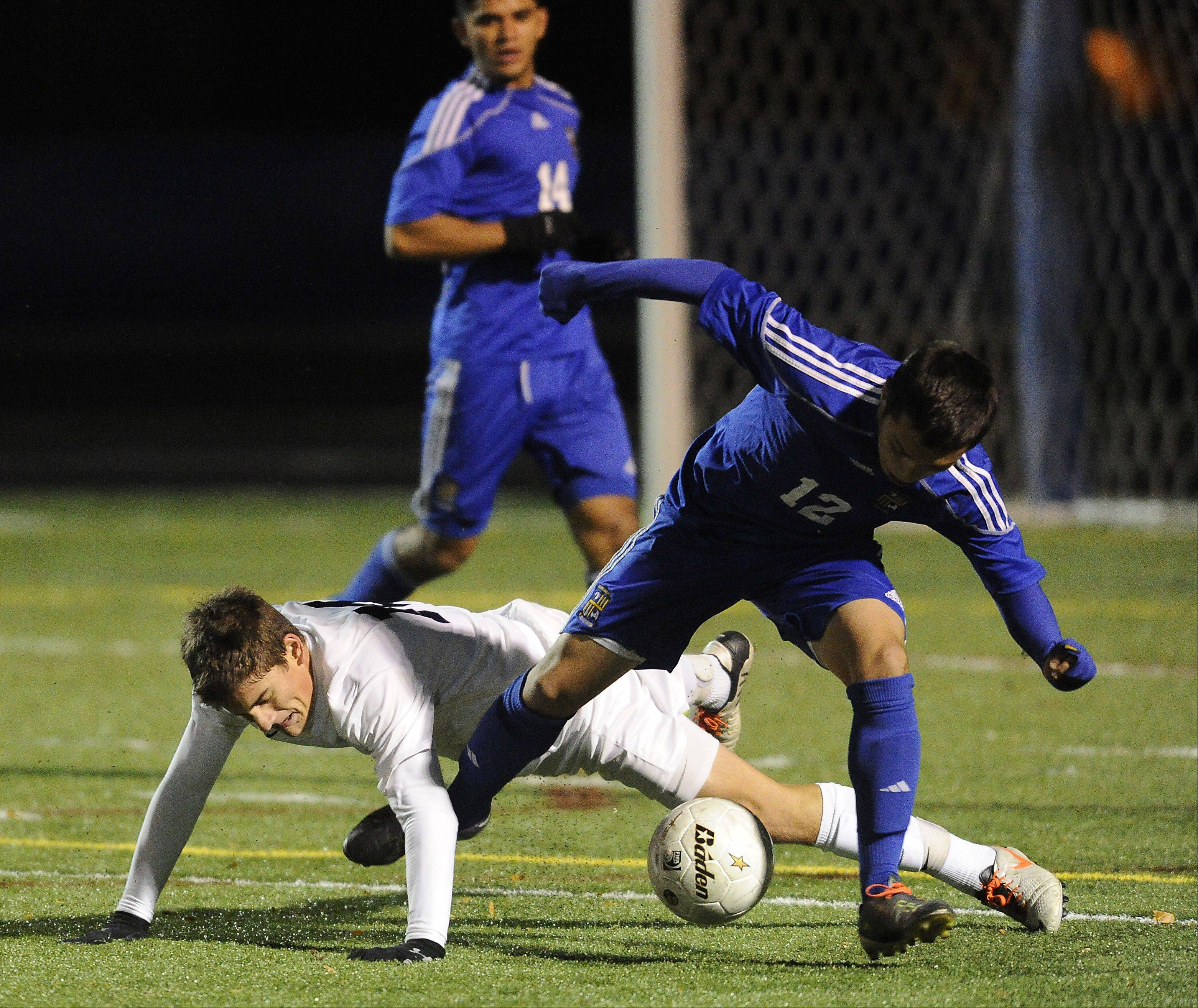 Wheeling's Alfredo Rocha gets tripped up by Lake Park's Giovanni Ciaccio in the second period of the Class 3A boys soccer state semifinals at Hoffman Estates on Friday.