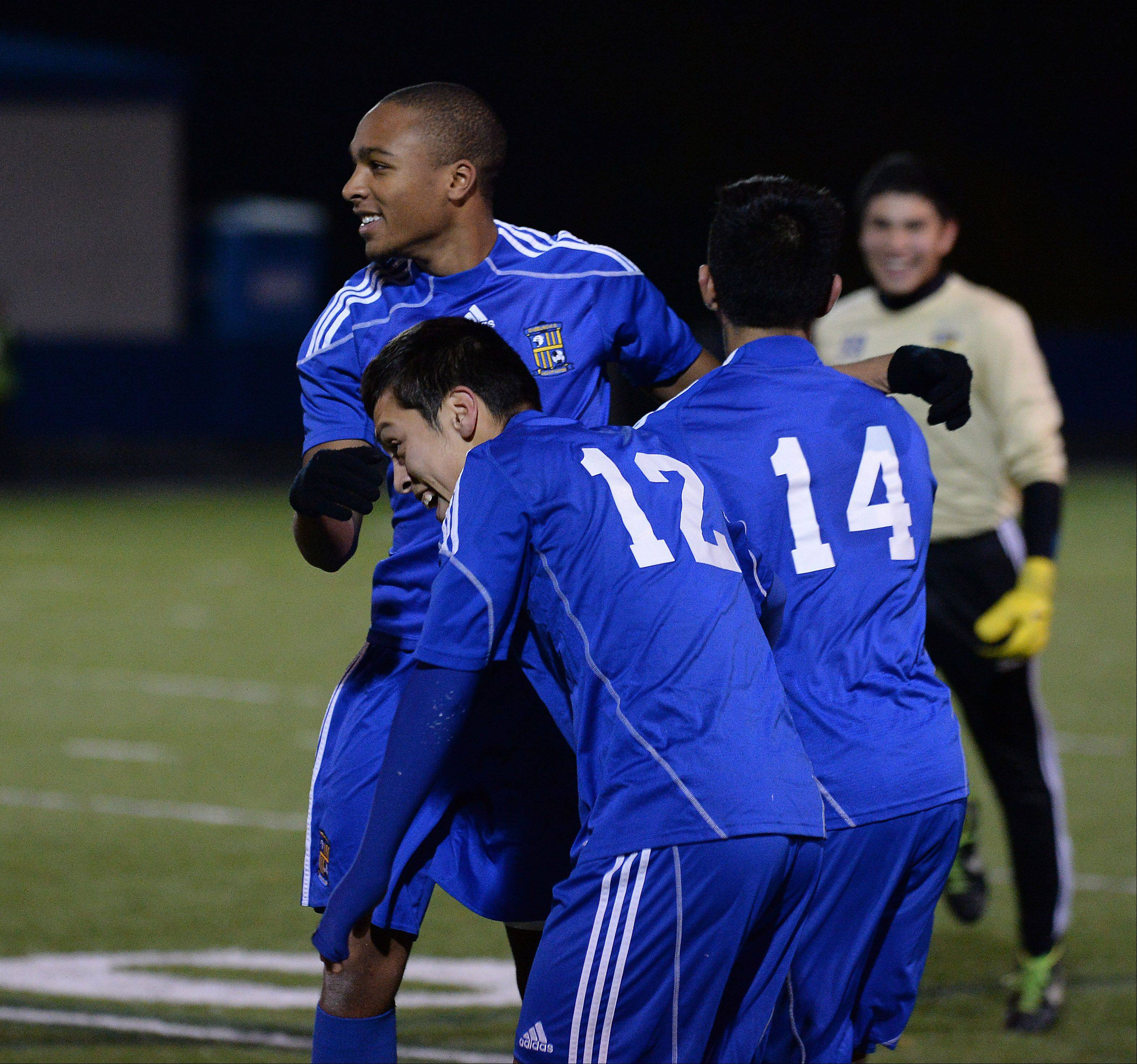 Wheeling's Laude Nathan celebrates their victory over Lake Park with his teammates Alfredo Rocha and Marino Lopez.