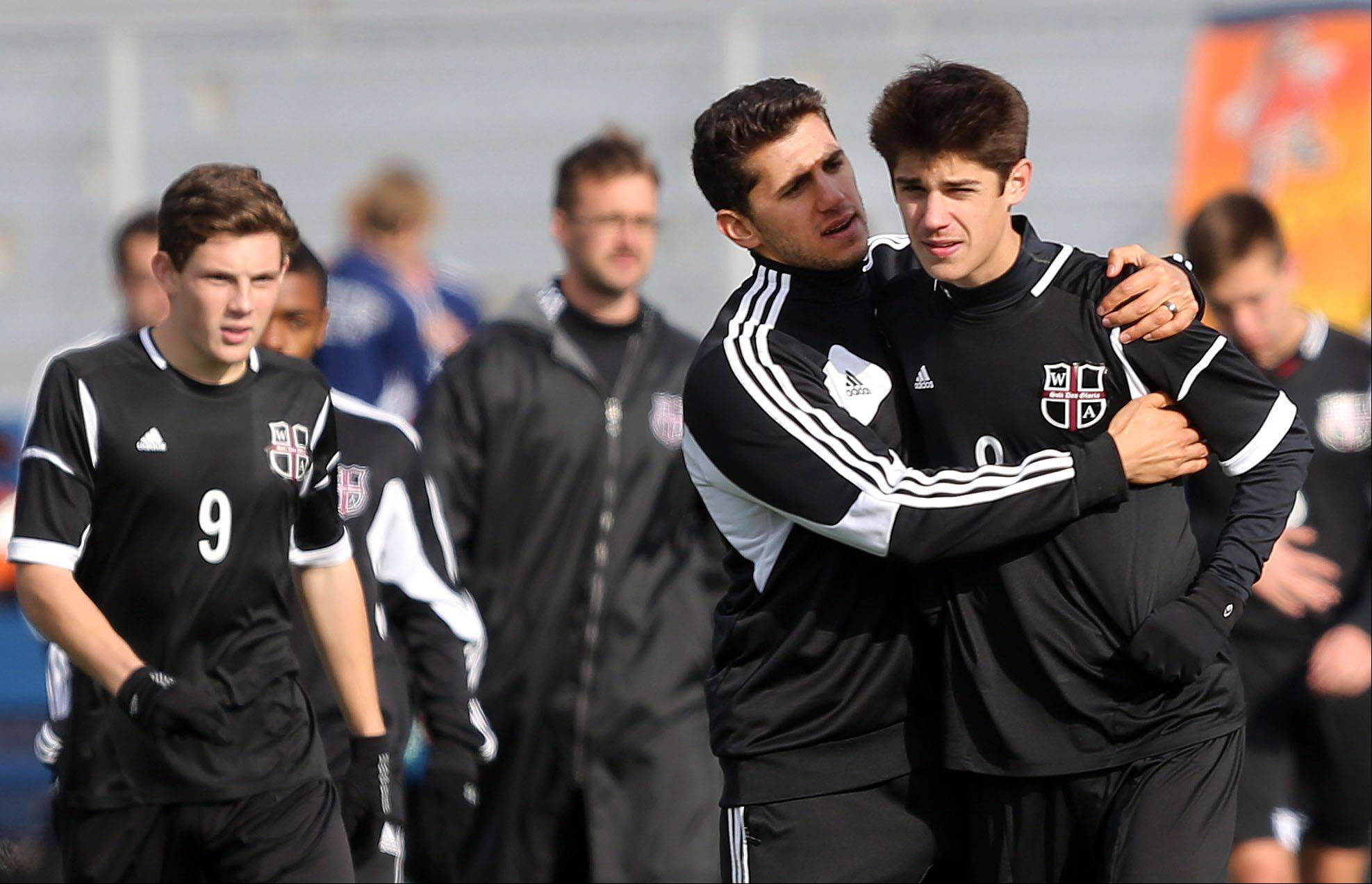 Wheaton Academy's Grant Rougas, right, is consoled by teammates after missing a kick in their shootout loss to St. Ignatius in Class 2A state semifinal game at Hoffman Estates High School Friday.