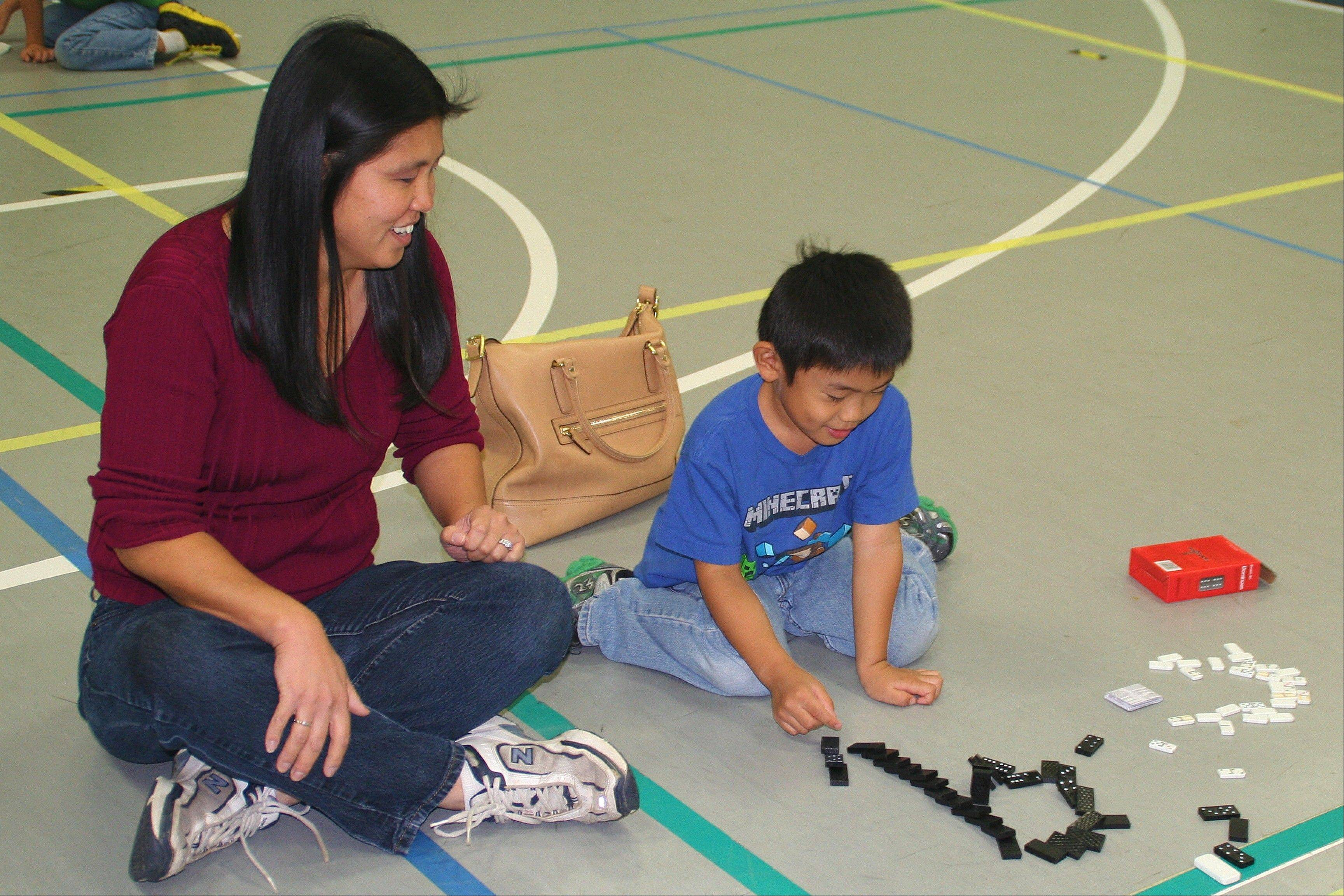 "Marcus Pasamba and his mom, Mae, create a lowercase ""Q"" domino fall at the Mother Son Dominoes and Pizza Event on Oct. 19."