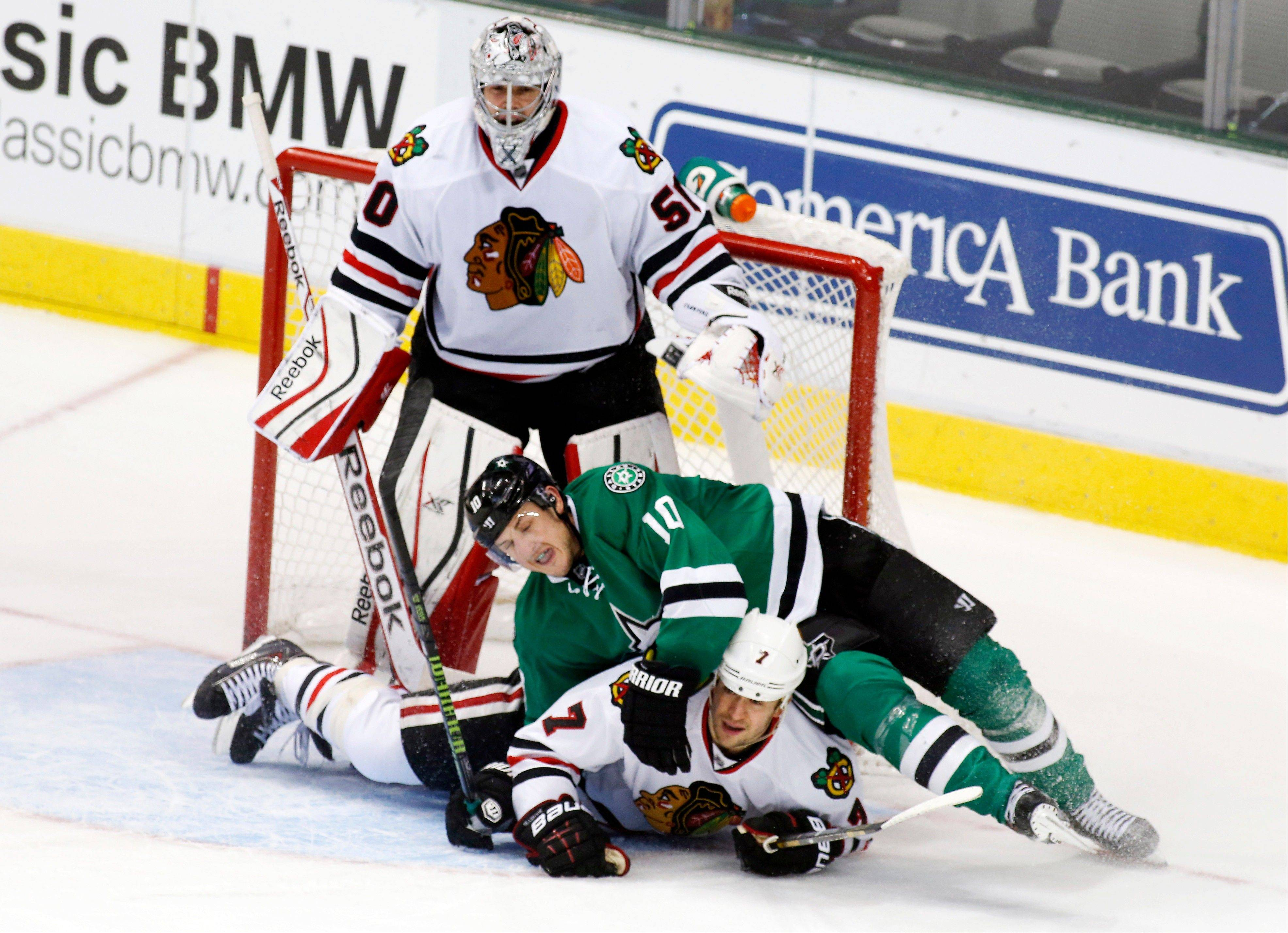 Blackhawks goalie Corey Crawford watches as defenseman Brent Seabrook gets tangled up with Shawn Horcoff of the Stars during the second period Saturday in Dallas, Texas.