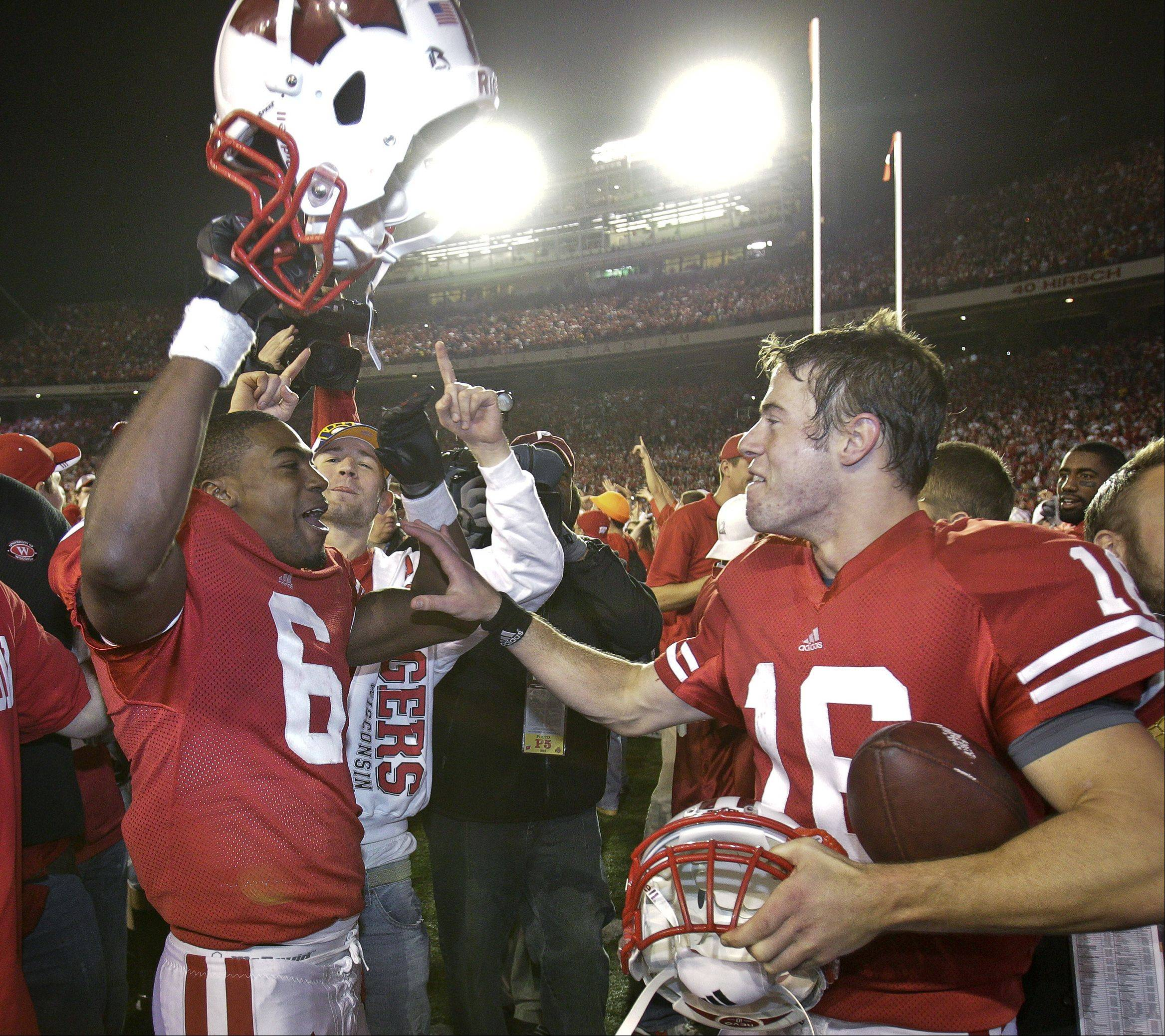 Wisconsin fans celebrate with Wisconsin wide receiver Isaac Anderson (6) and quarterback Scott Tolzien (16) after Wisconsin upset No. 1 Ohio State 31-18 in an NCAA college football game Saturday, Oct. 16, 2010, in Madison, Wis.