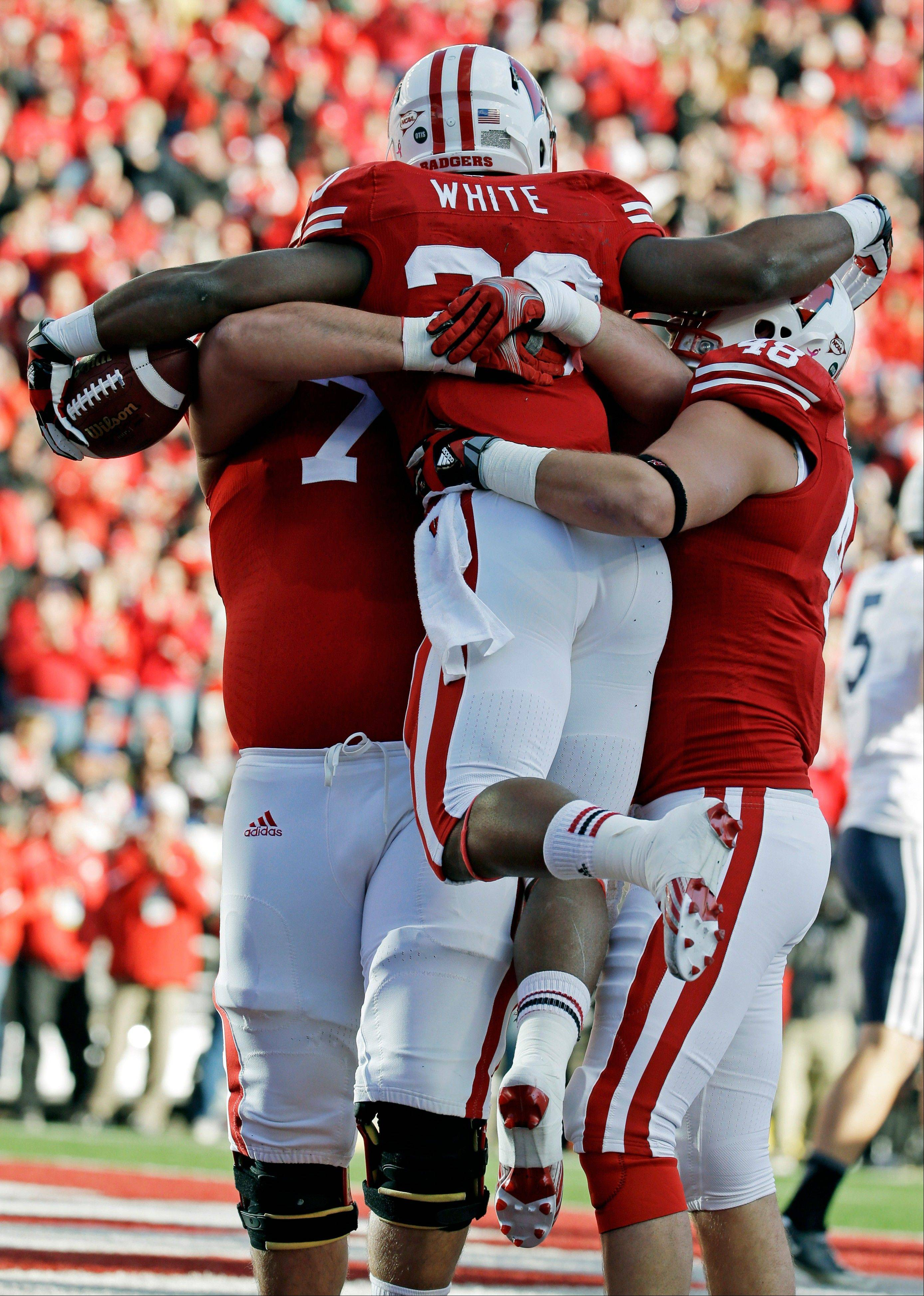 Wisconsin�s James White, center, celebrates a touchdown run with teammates Rob Havenstein (78) and Jacob Pedersen (48) during Saturday�s game against Brigham Young in Madison.