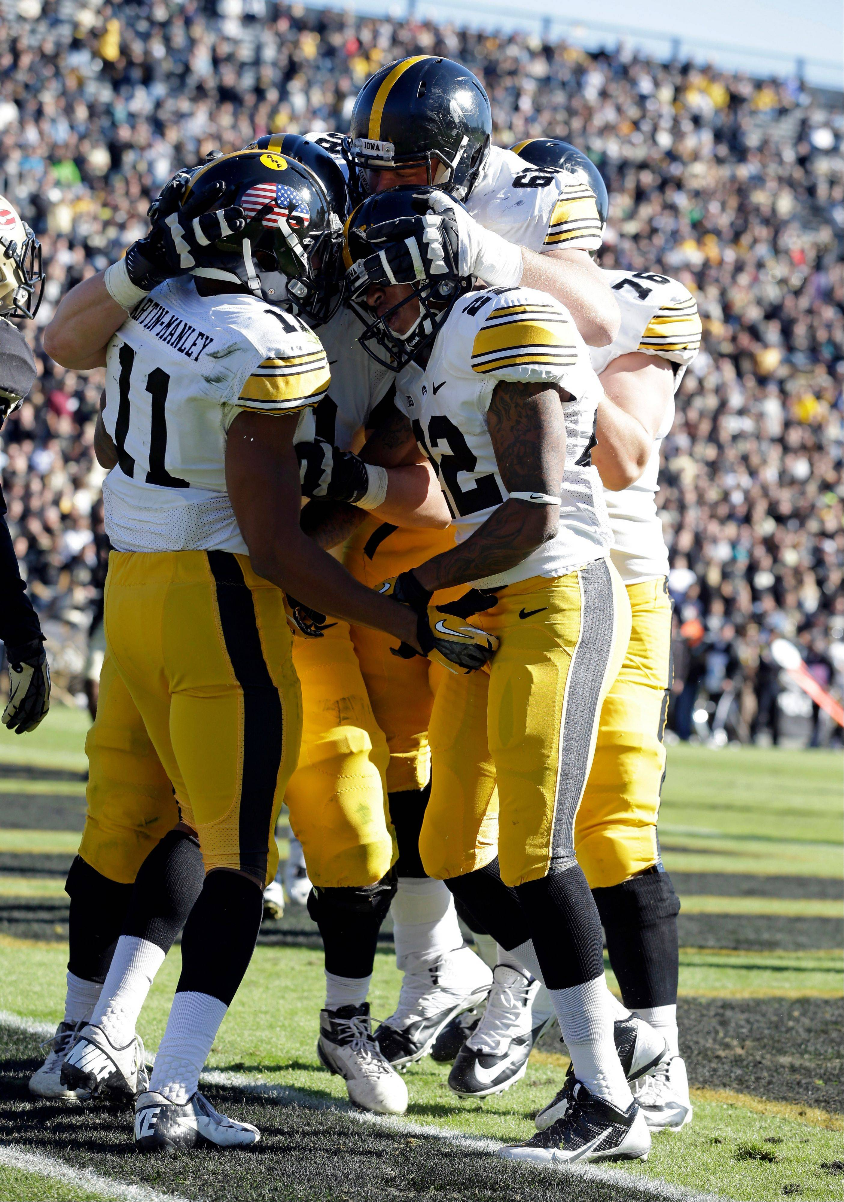 Iowa wide receiver Kevonte Martin-Manley (11) celebrates with tight end Ray Hamilton, right, and offensive linesman Brandon Scherff after scoring a touchdown against Purdue during the first half of an NCAA college football game in West Lafayette, Ind., Saturday, Nov. 9, 2013. (AP Photo/Michael Conroy)