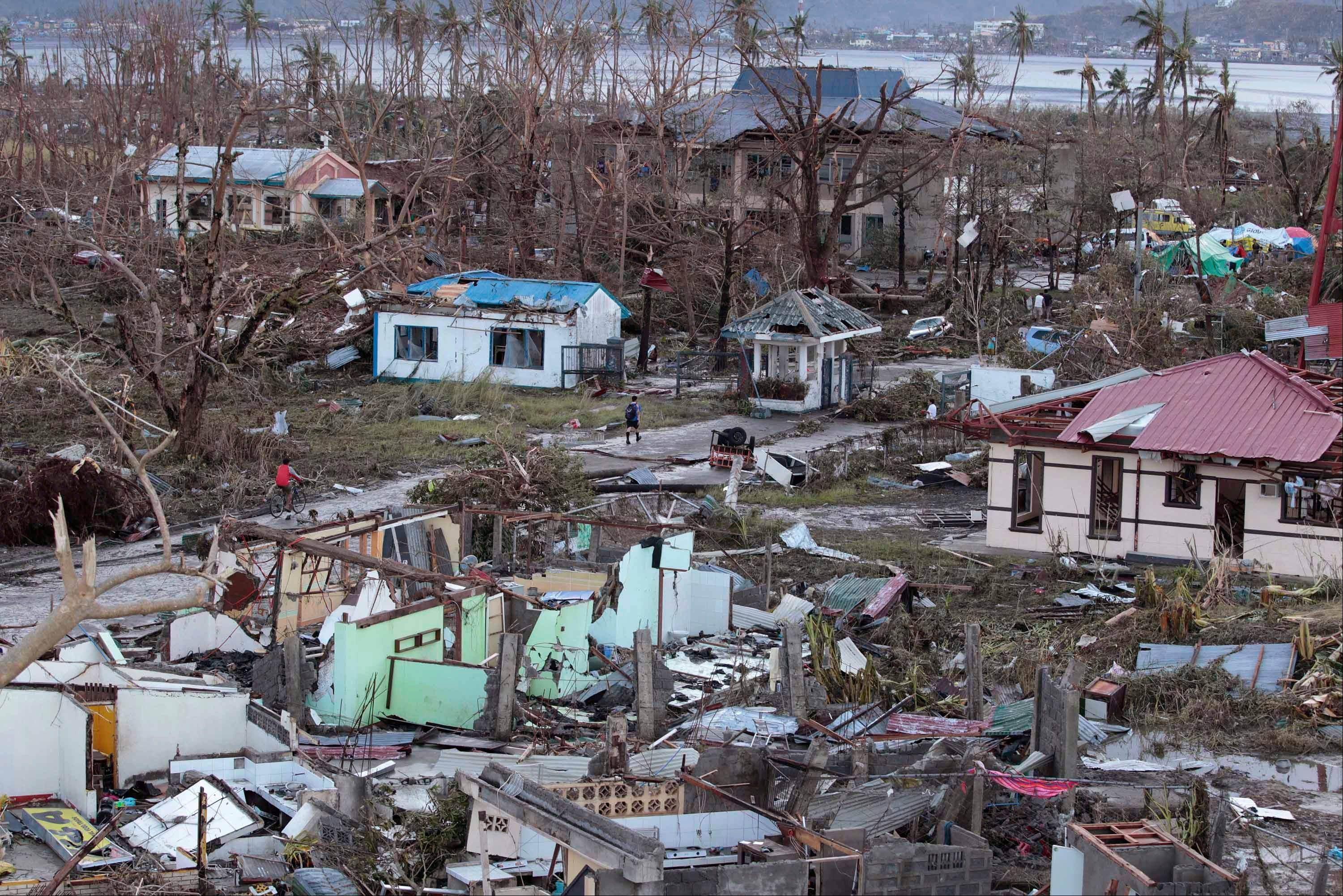A resident walks by remains of houses Saturday after powerful Typhoon Haiyan slammed into Tacloban city, Leyte province central Philippines.