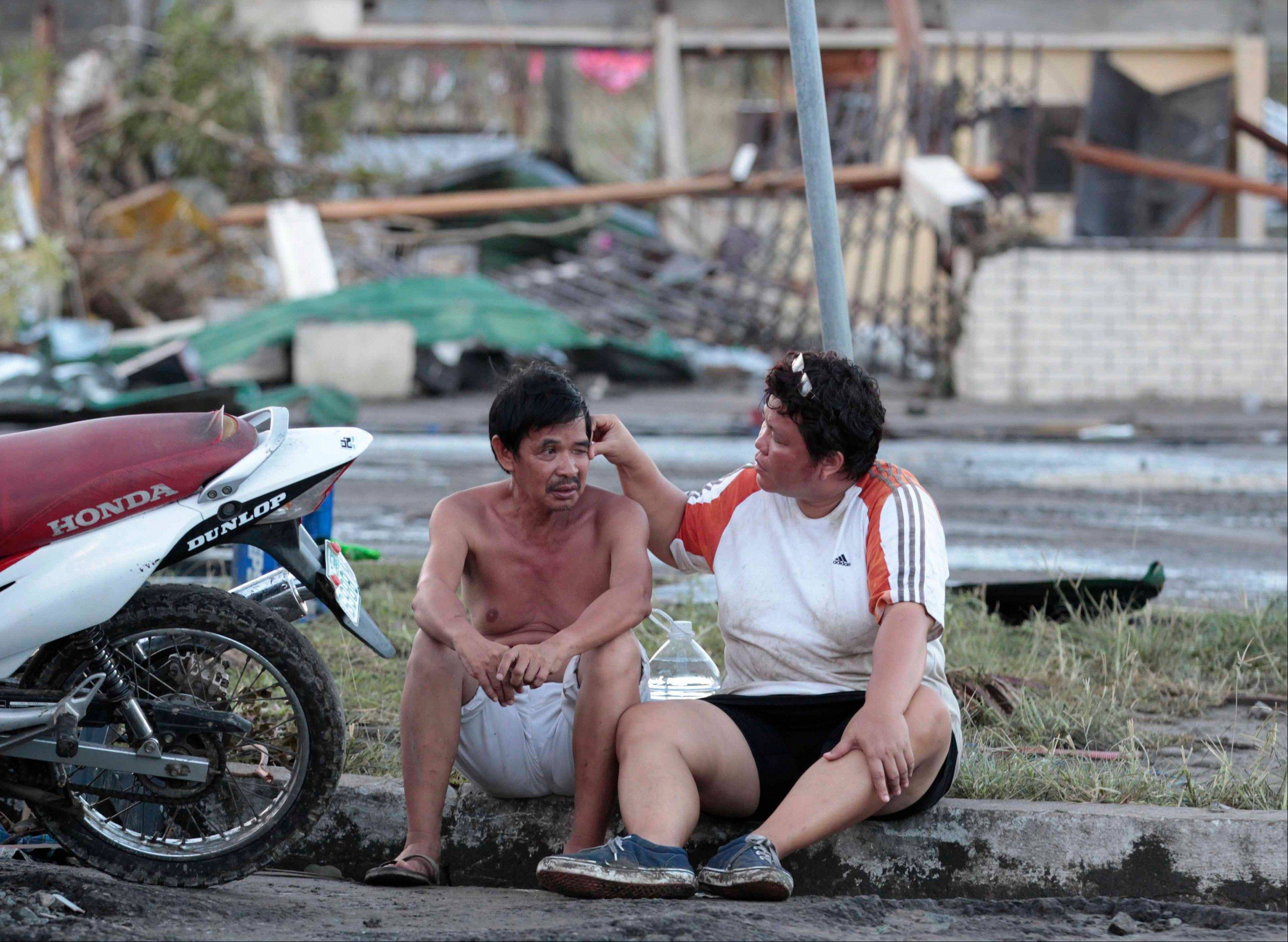 Residents sit outside their damaged house Saturday after Haiyan plowed through Tacloban city, Leyte province, central Philippines.