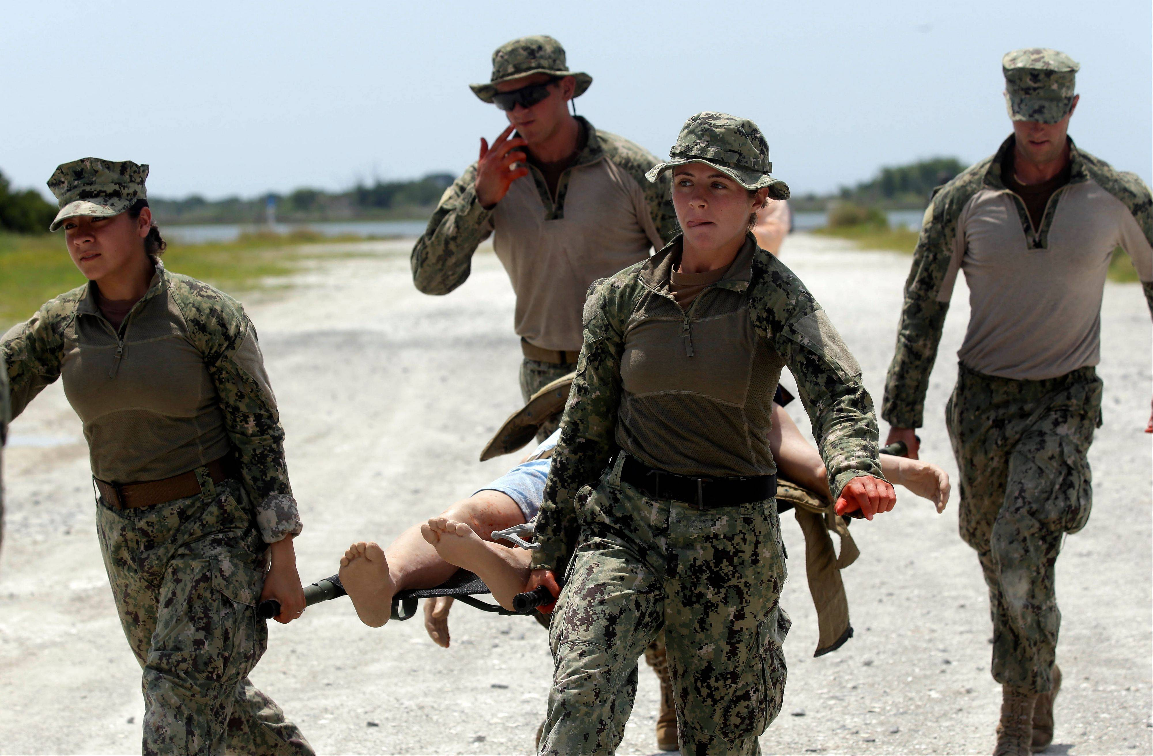 Schnatzmeyer, front left, and Hinchliff, right, both of Coastal Riverine Squadron 2, carry a mock wounded person as they participate in a U.S. Navy Riverine Crewman Course.