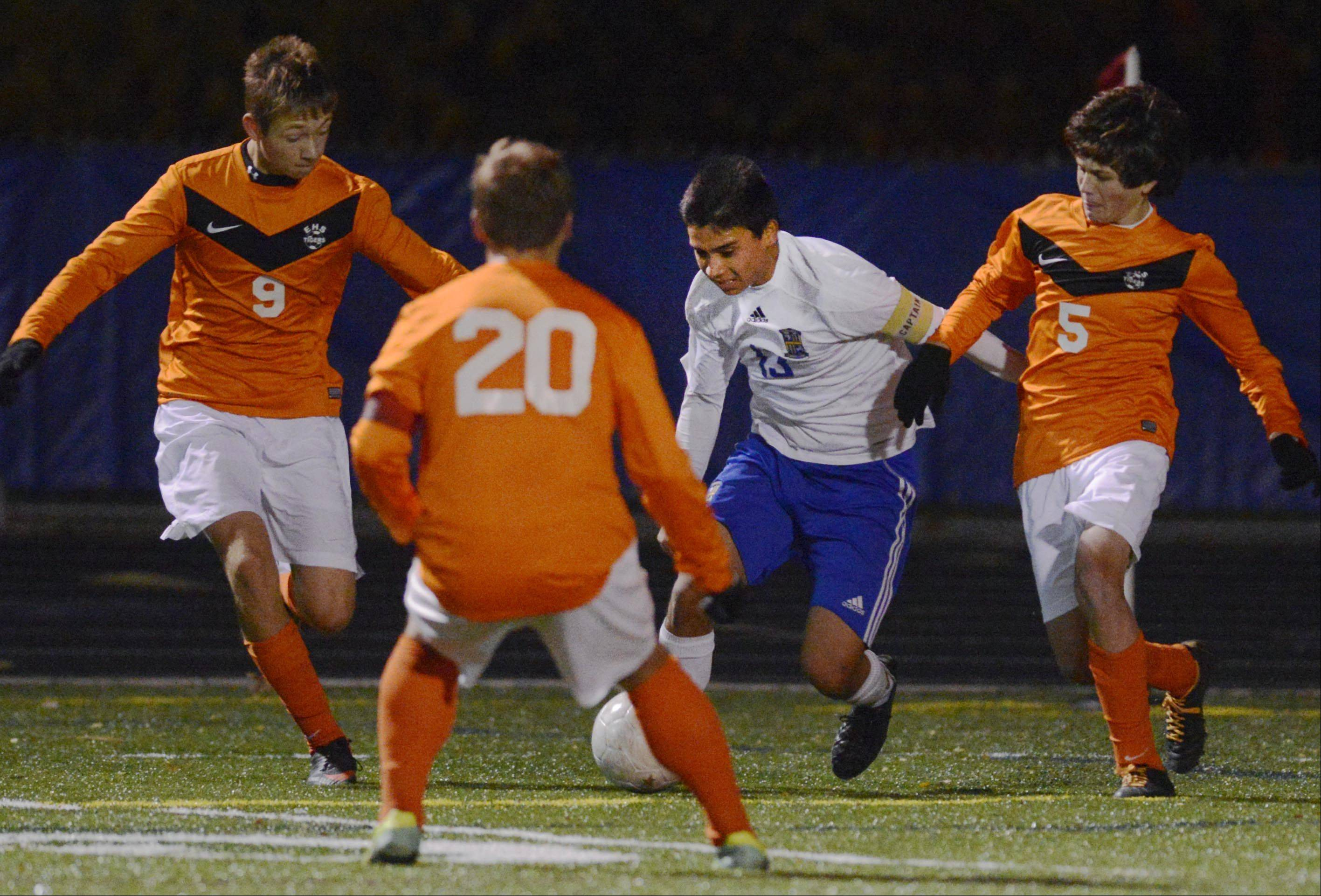 Wheeling's Jose Garcia is surrounded by Edwardsville players as he tries to center the ball in front of the net in the Class 3A soccer state championship game Saturday night in Hoffman Estates.