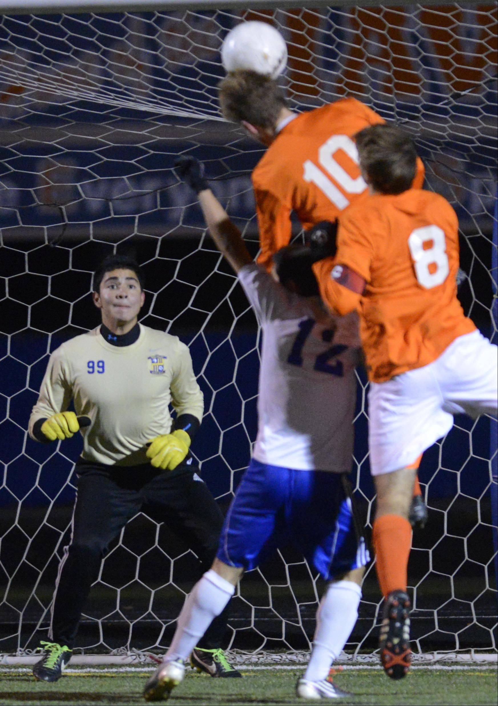 Wheeling goalkeeper Gary Mendoza defends the net as teammate Alfredo Rocha tries to stop Edwardsville's Landon Paul from sending a header into the net in the Class 3A soccer state championship game Saturday night in Hoffman Estates. Mendoza stopped the shot.