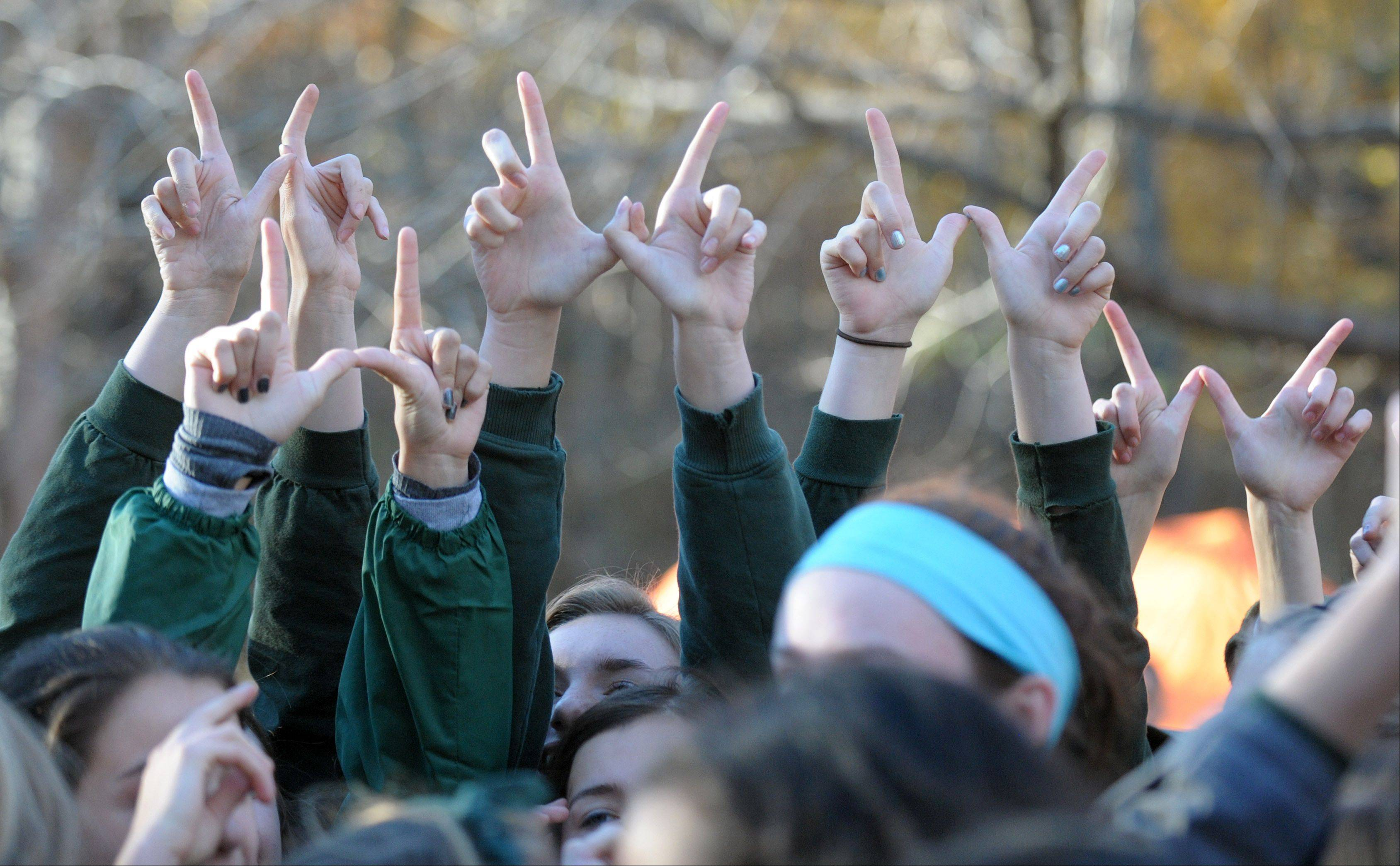"The Glenbard West girls team forms ""W""s with their hands after learning they took the Class 3A championship at the IHSA cross country state finals at Detweiller Park in Peoria on Saturday, November 9."
