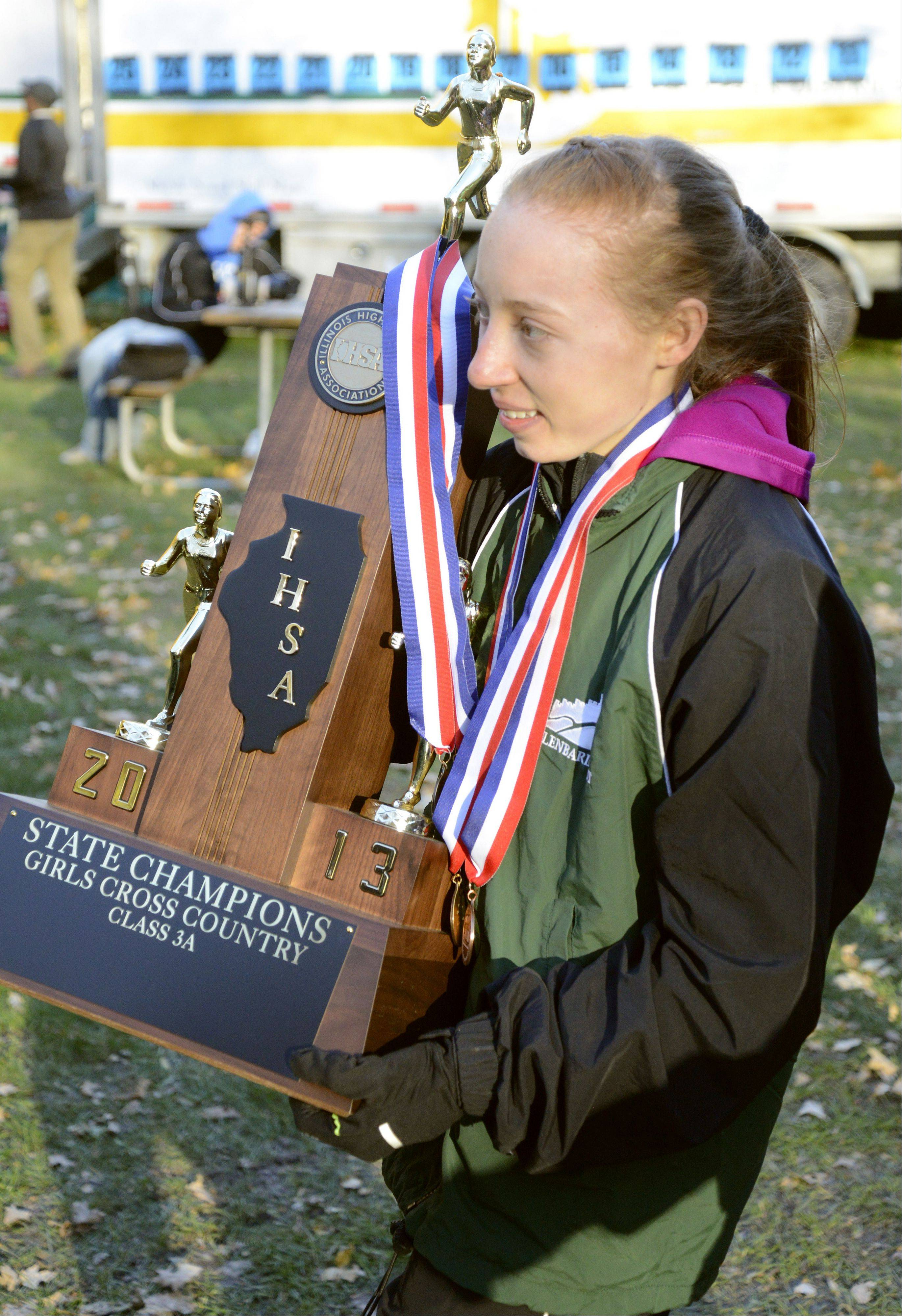 Glenbard West's Madeline Perez carries the team's Class 3A first place trophy at the IHSA cross country state finals at Detweiller Park in Peoria on Saturday, November 9.