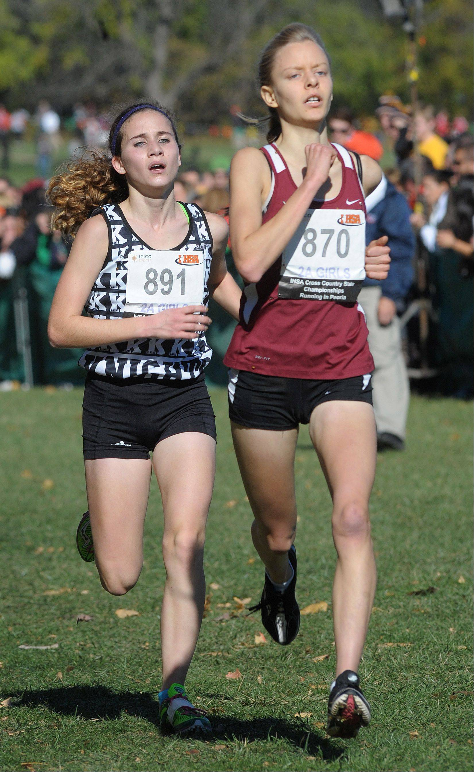 Kaneland's Brianna Bower (891) and Montini's Maggie Hallerud (870) battle to the finish line in the Class 2A IHSA cross country state final at Detweiller Park in Peoria on Saturday, November 9.