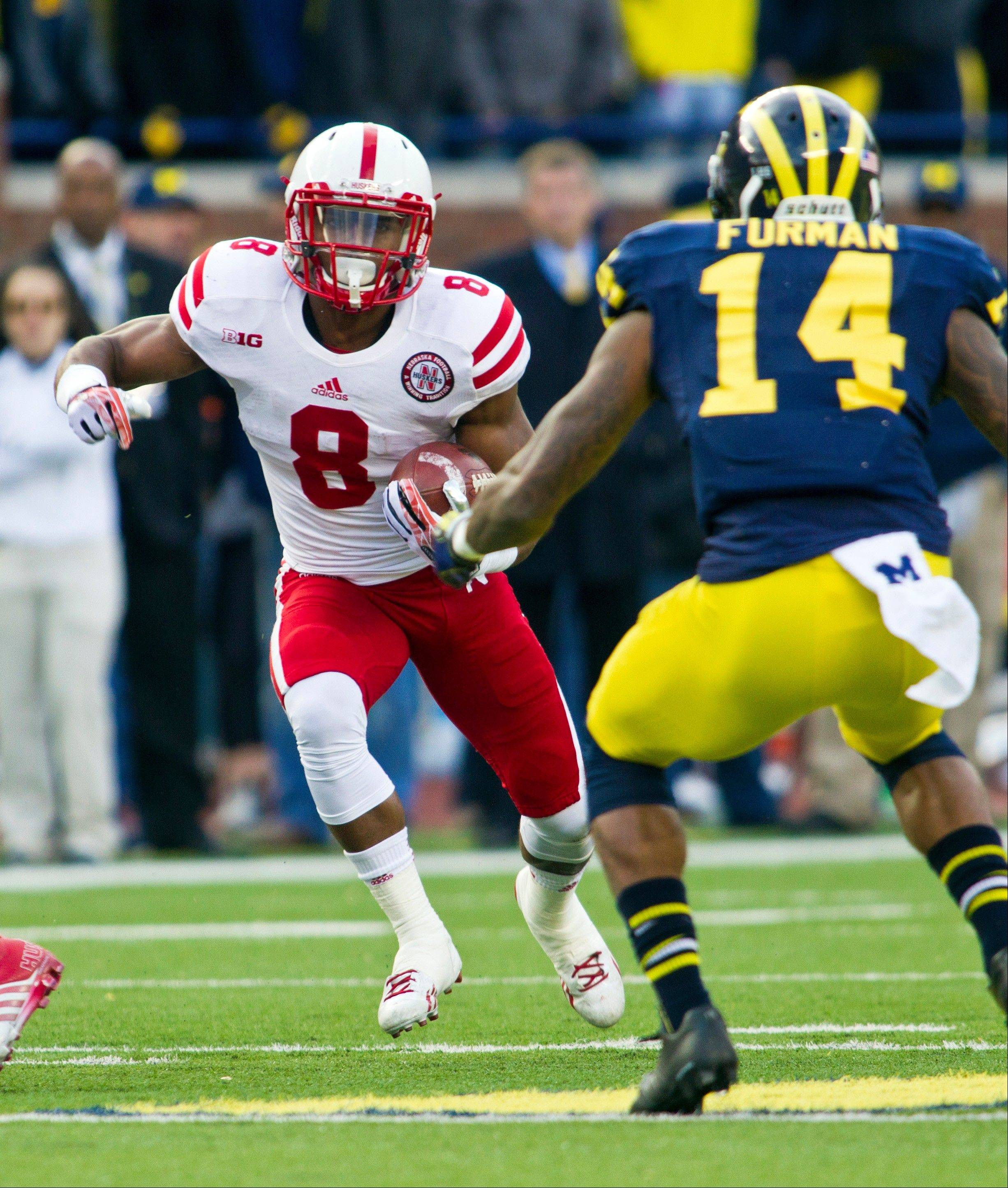 Nebraska running back Ameer Abdullah (8) rushes into coverage by Michigan safety Josh Furman (14) during Saturday's game in Ann Arbor, Mich. The Huskers beat the Wolverines 17-13.
