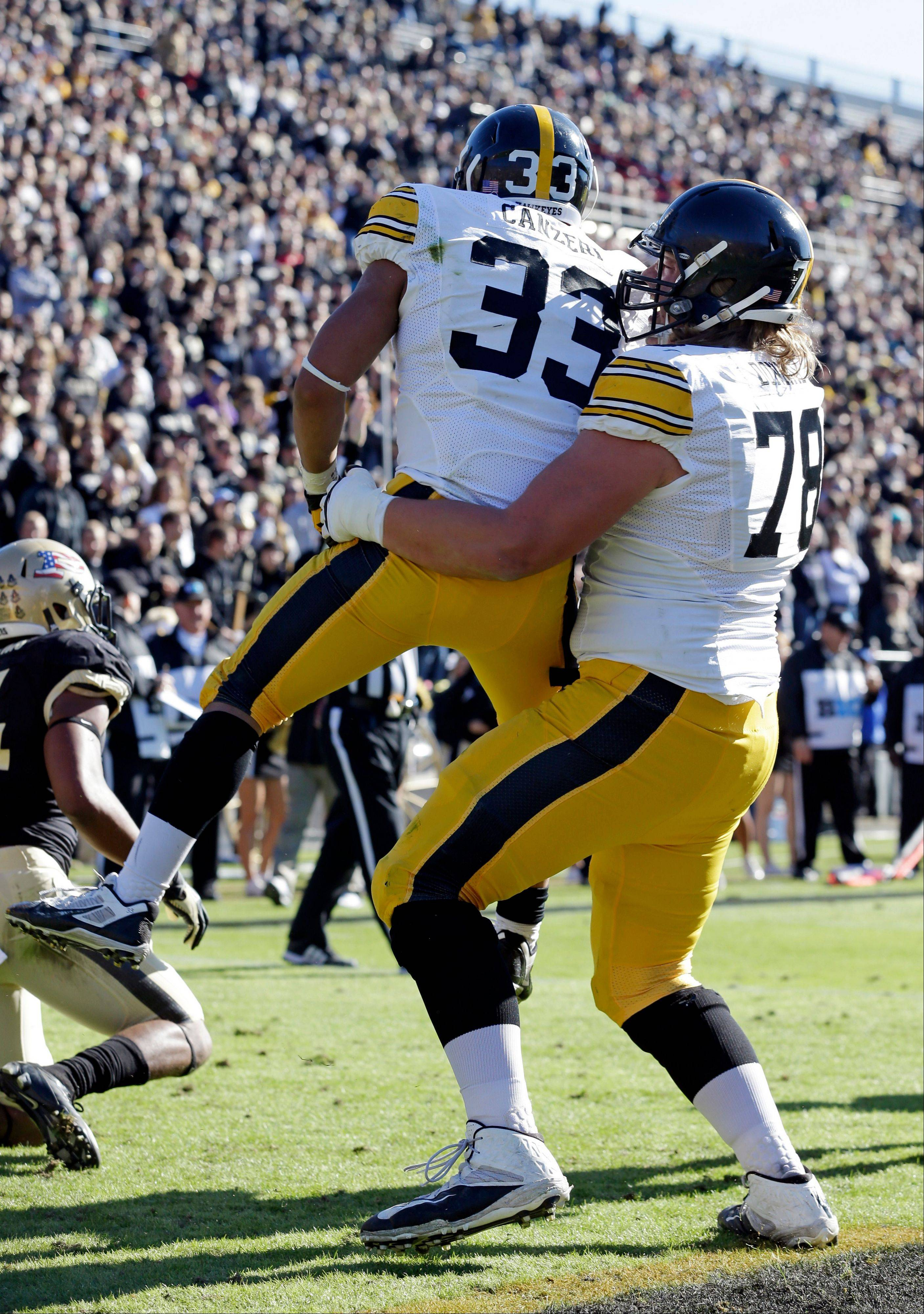 Iowa running back Jordan Canzeri (33) is hoisted by offensive linesman Andrew Donnal after scoring a touchdown against Purdue during the first half of an NCAA college football game in West Lafayette, Ind., Saturday, Nov. 9, 2013.