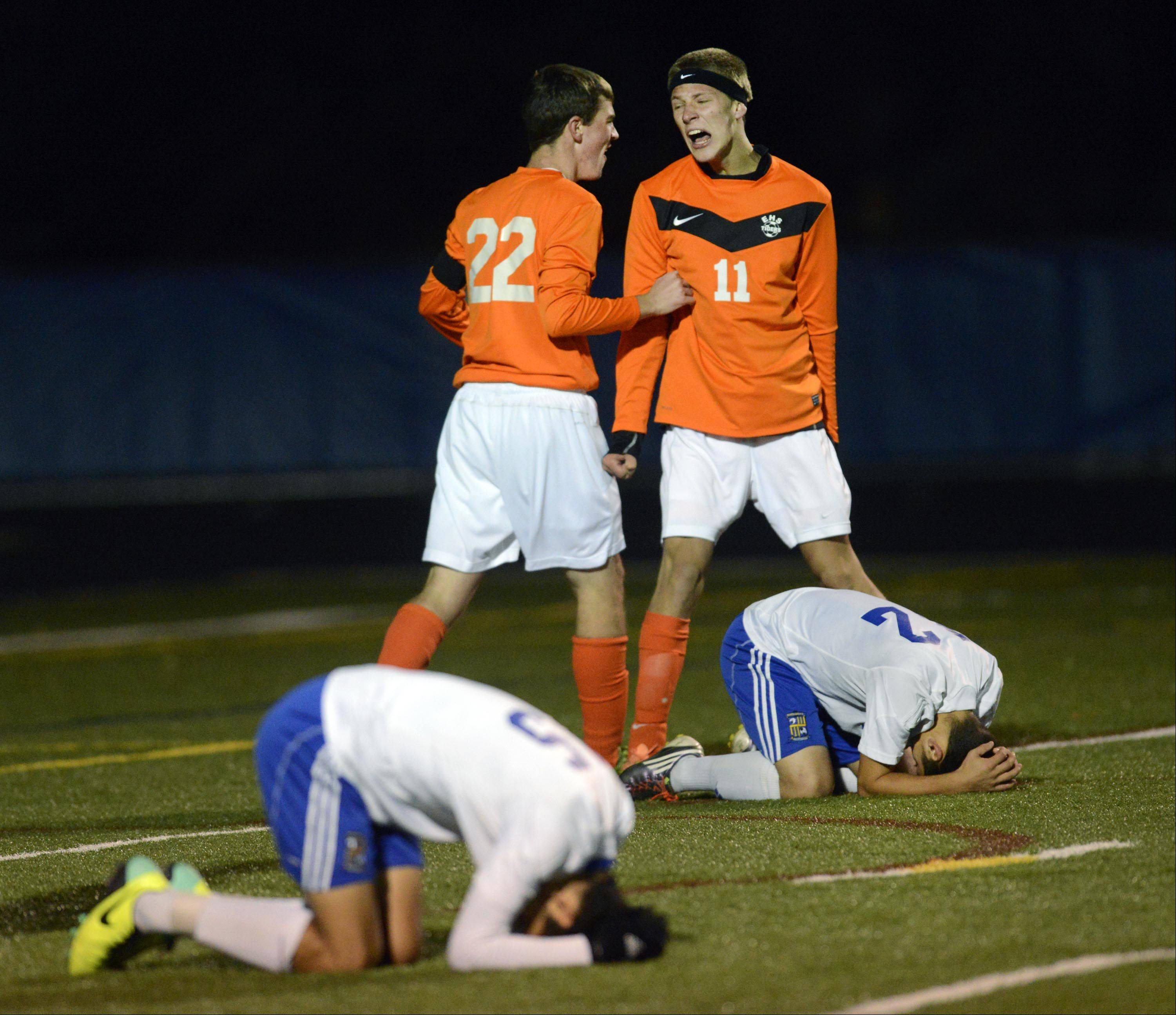 John Starks/jstarks@dailyherald.com Wheeling's Michael hernandez, foreground, and Alfredo Rocha, fall to the turf as Edwardsville's Hayden Hessler and Justin Lowry celebrate their 2-1 victory in the Class 3A soccer state championship game Saturday night in Hoffman Estates.