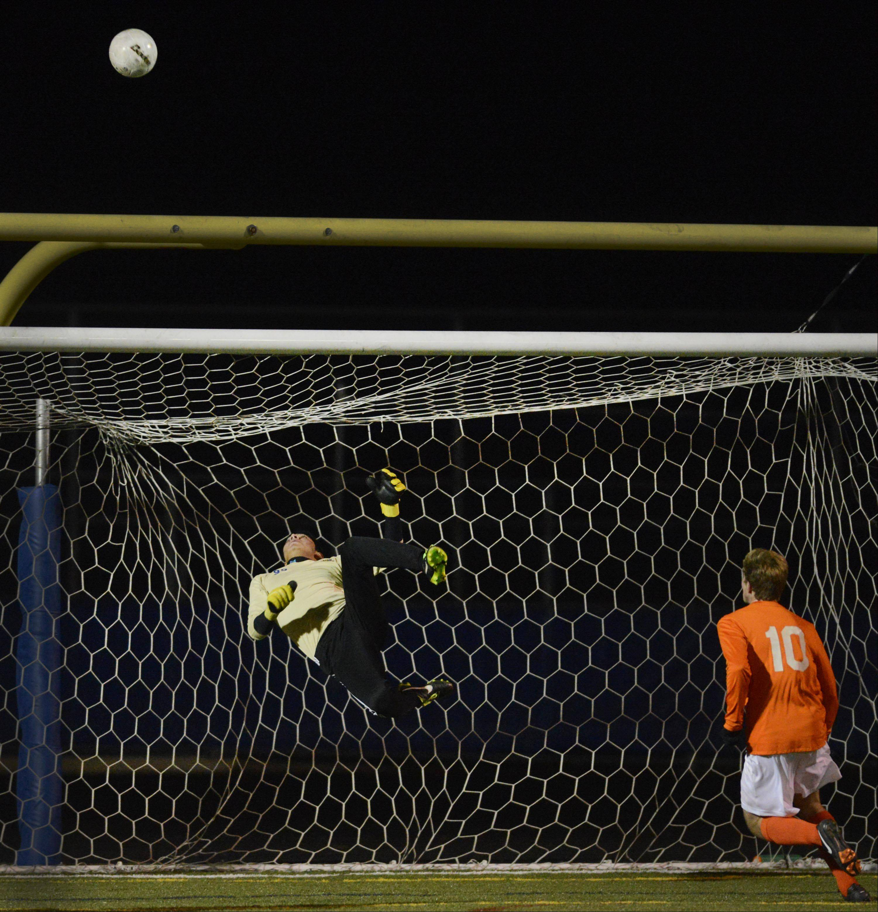 John Starks/jstarks@dailyherald.comWheeling goalkeeper Gary Mendoza watches a shot he deflected from Edwardsville's Lando Paul bounce up over the net in the Class 3A soccer state championship game Saturday night in Hoffman Estates.
