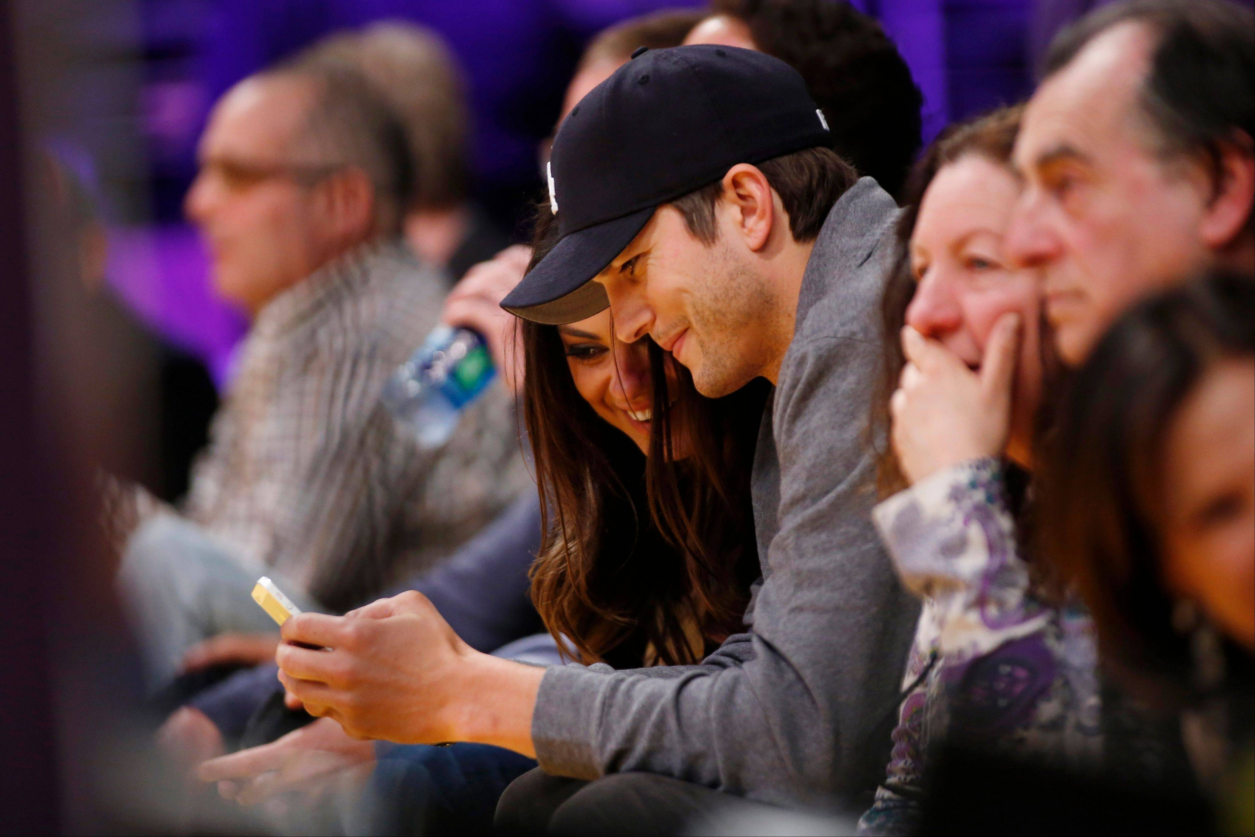 Actors Mila Kunis, left, and Ashton Kutcher look at a mobile phone as they sit courtside together at the NBA basketball game between the Phoenix Suns and Los Angeles Lakers, in Los Angeles. Kutcher is included on a long list of celebrities who — at one time or another — have taken a break from Twitter. Twitter burnout among celebrities, athletes and shameless self-promoters poses a risk to the company and its investors.