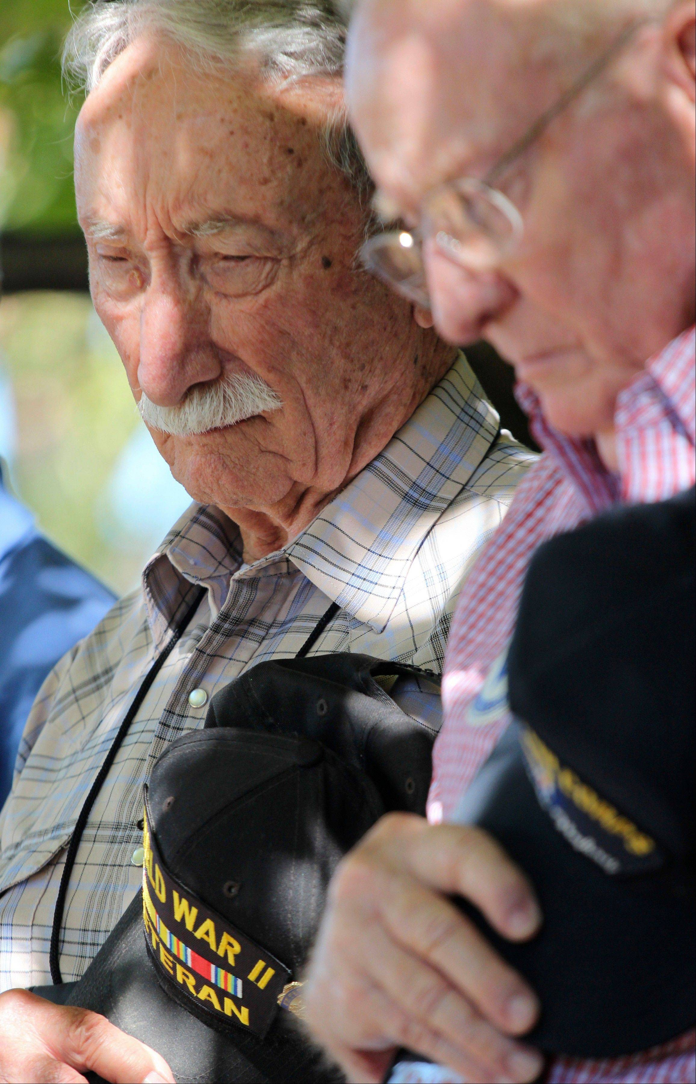 In this Sept. 27, 2013 photo, George Williams, left, and Robert Crouse, bow their heads as they take part in a memorial ceremony during a reunion outside the U.S. Air Force Museum at Wright Patterson Air Force base in Dayton, Ohio. As many as 11,000 people, including Williams and Crouse, served in the 57th Bomb Wing that flew missions over German-held Europe from North Africa and the island of Corsica during most of the war. Hundreds survive, according to wing historians and reunion organizers. Only nine veterans made it to this fall�s event.