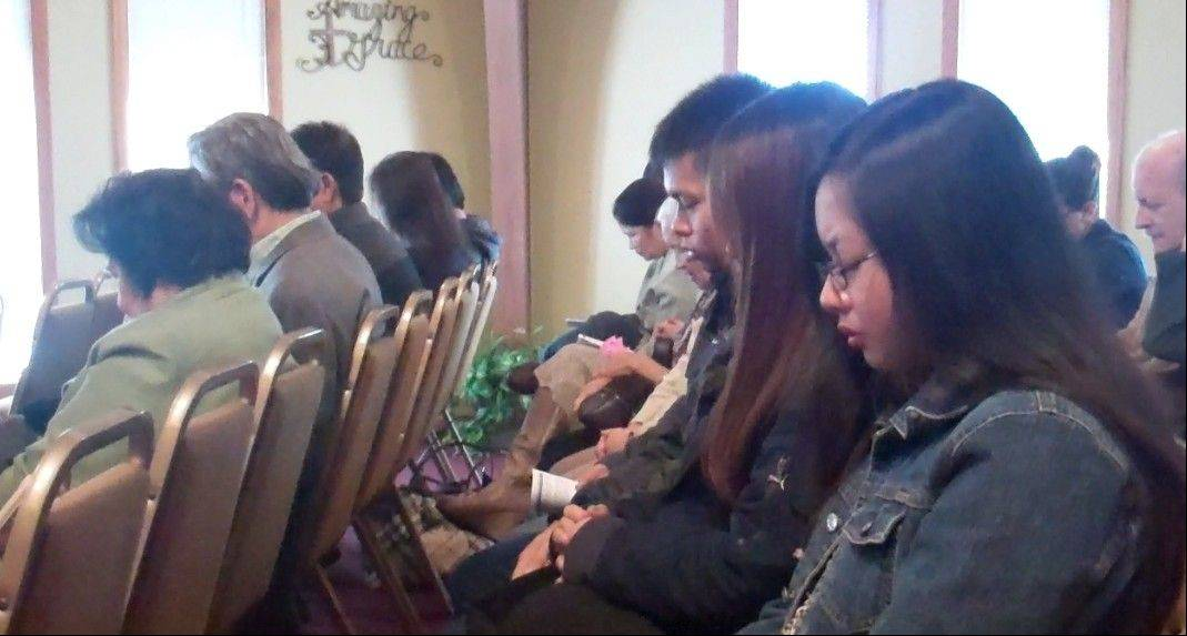 Parishioners at Northwest Filipino Baptist in Elk Grove Village pray for victims of Typhoon Haiyan in the Philippines during Sunday's service. Many church members are still waiting to hear from family members in the Philippines who may have been impacted by the deadly storm.