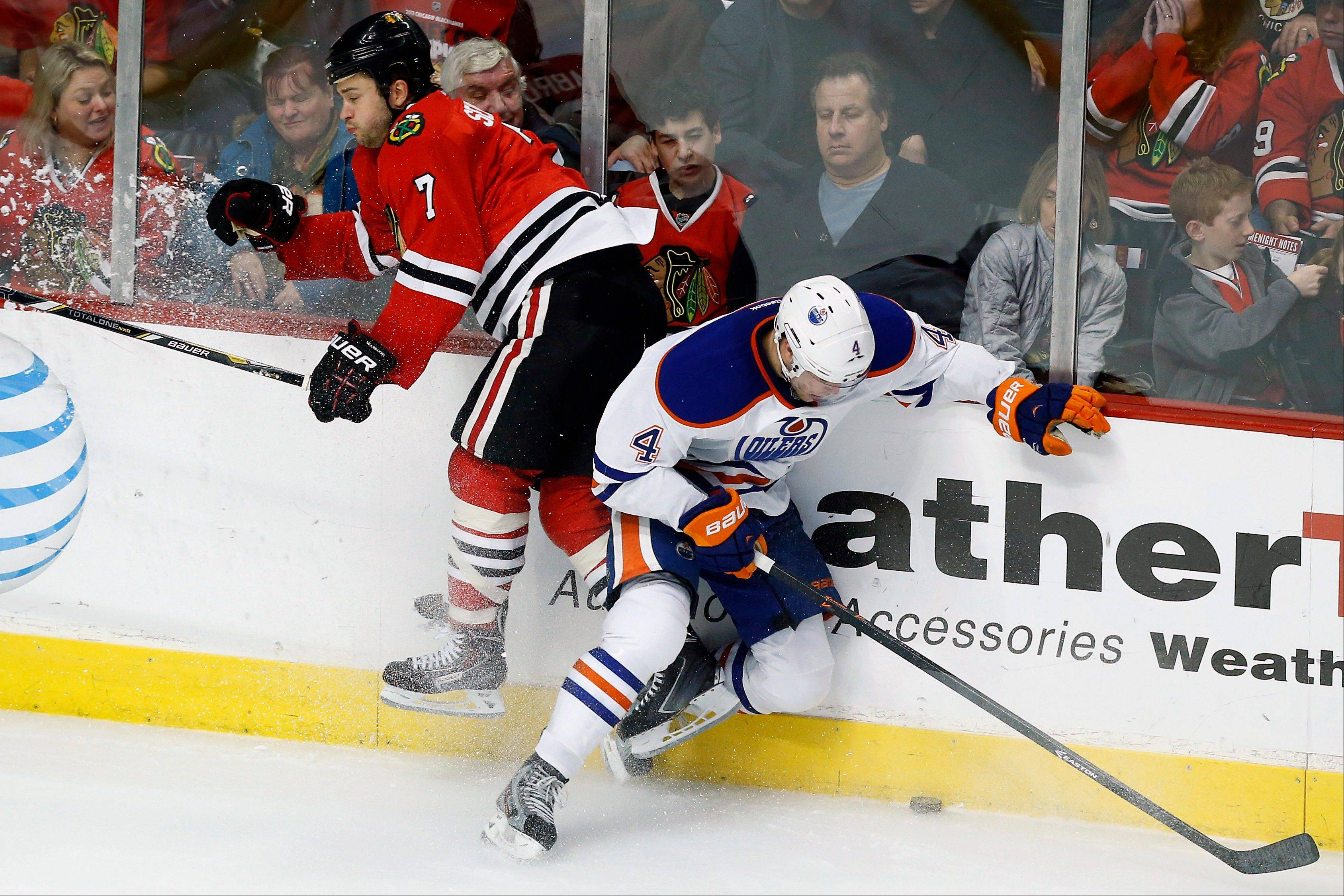 Blackhawks defenseman Brent Seabrook (7) and Edmonton Oilers left wing Taylor Hall (4) hit the glass over the puck during the second period of an NHL hockey game on Sunday, Nov. 10, 2013, in Chicago.