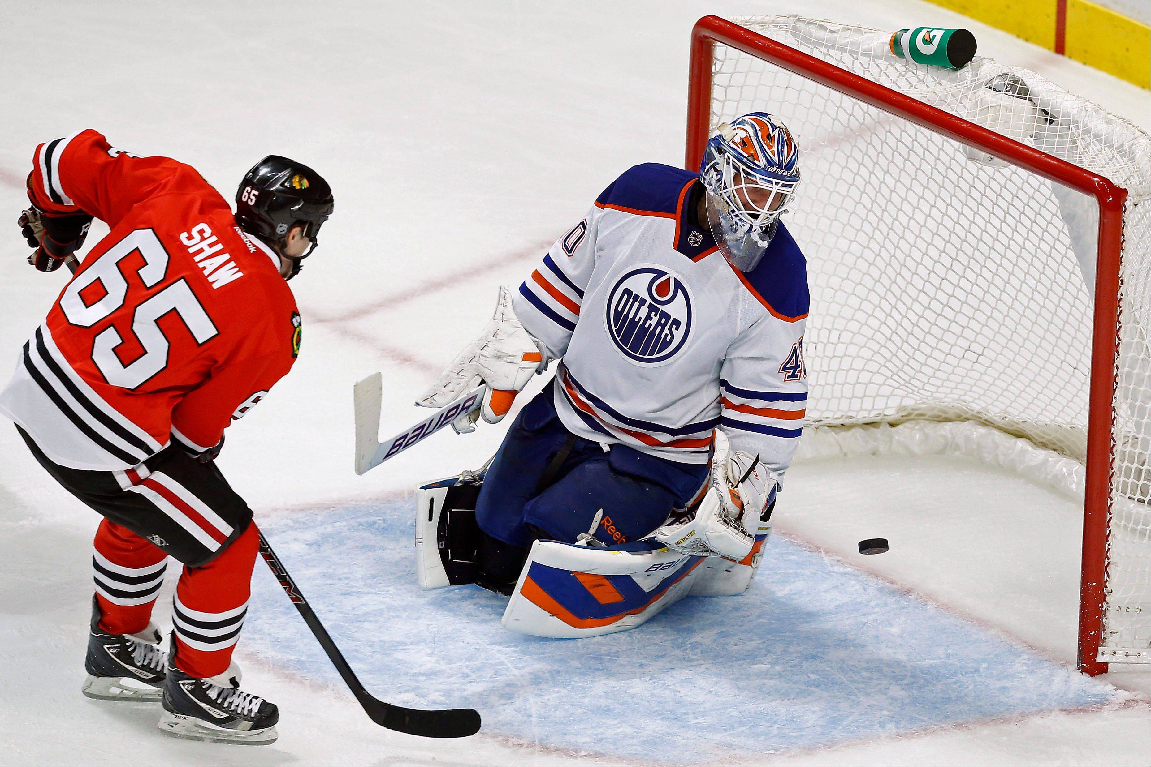 Blackhawks center Andrew Shaw scores a goal past Edmonton Oilers goalie Devan Dubnyk (40) during the second period of the NHL hockey game on Sunday, Nov. 10, 2013, in Chicago.