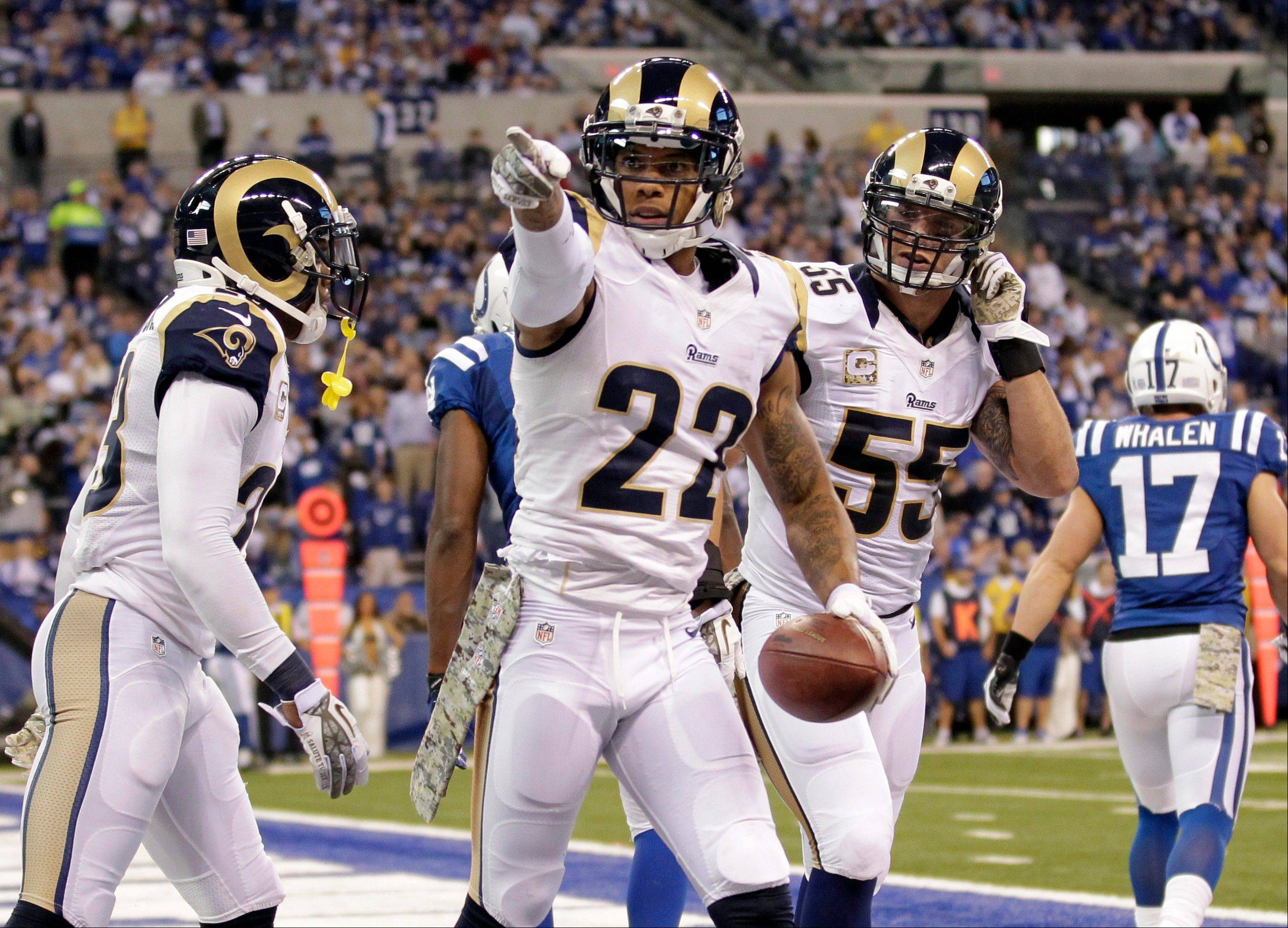 St. Louis Rams cornerback Trumaine Johnson, center, celebrates an interception with teammates James Laurinaitis (55) and free safety Rodney McLeod during the second half of an NFL football game against the Indianapolis Colts in Indianapolis, Sunday, Nov. 10, 2013.