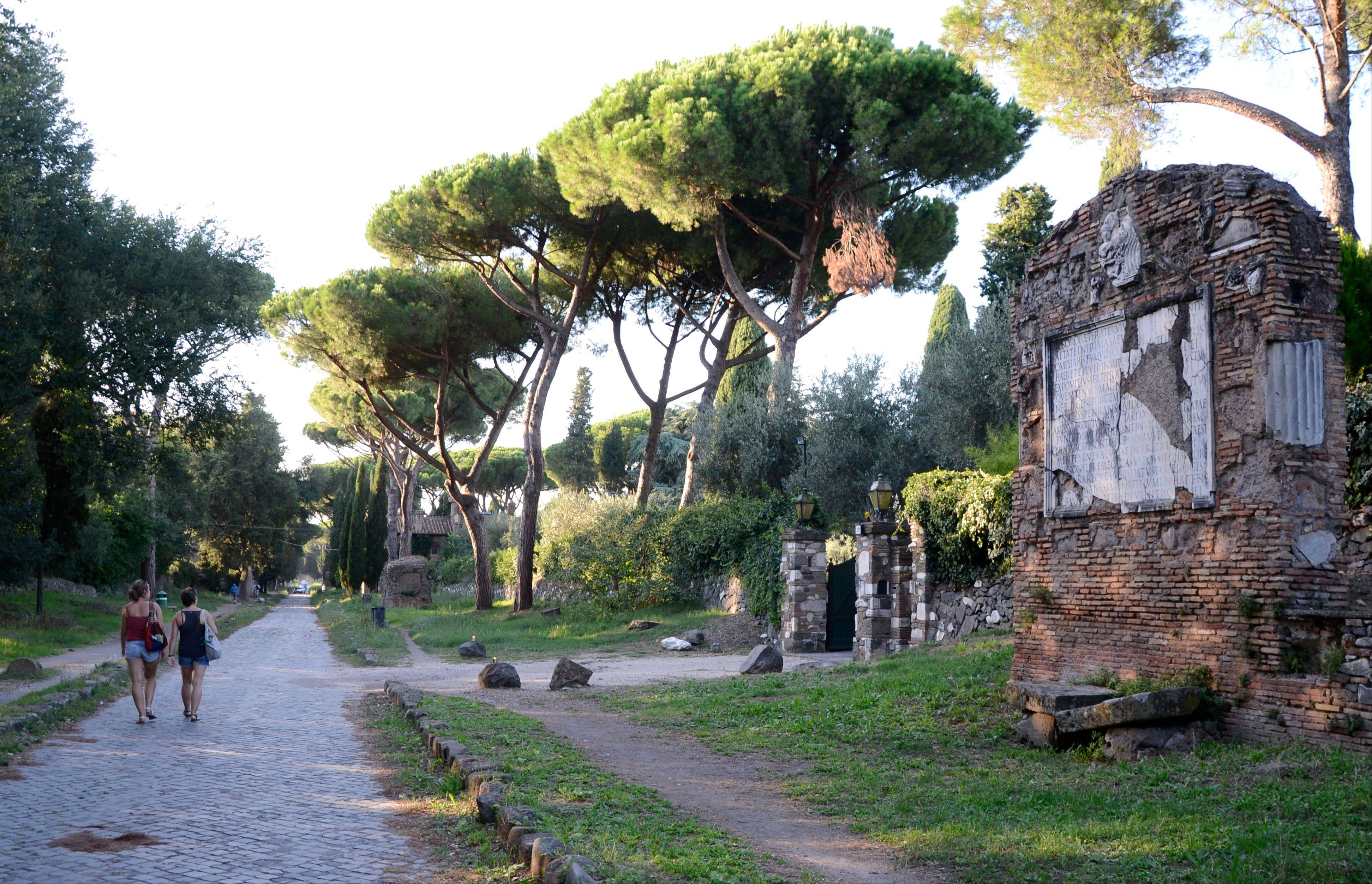 People walk past ruins along the Appia Antica, the ancient Roman Appian Way, in Rome. A walk on the Appia is a wonderful way to feel the city's past beneath your feet.