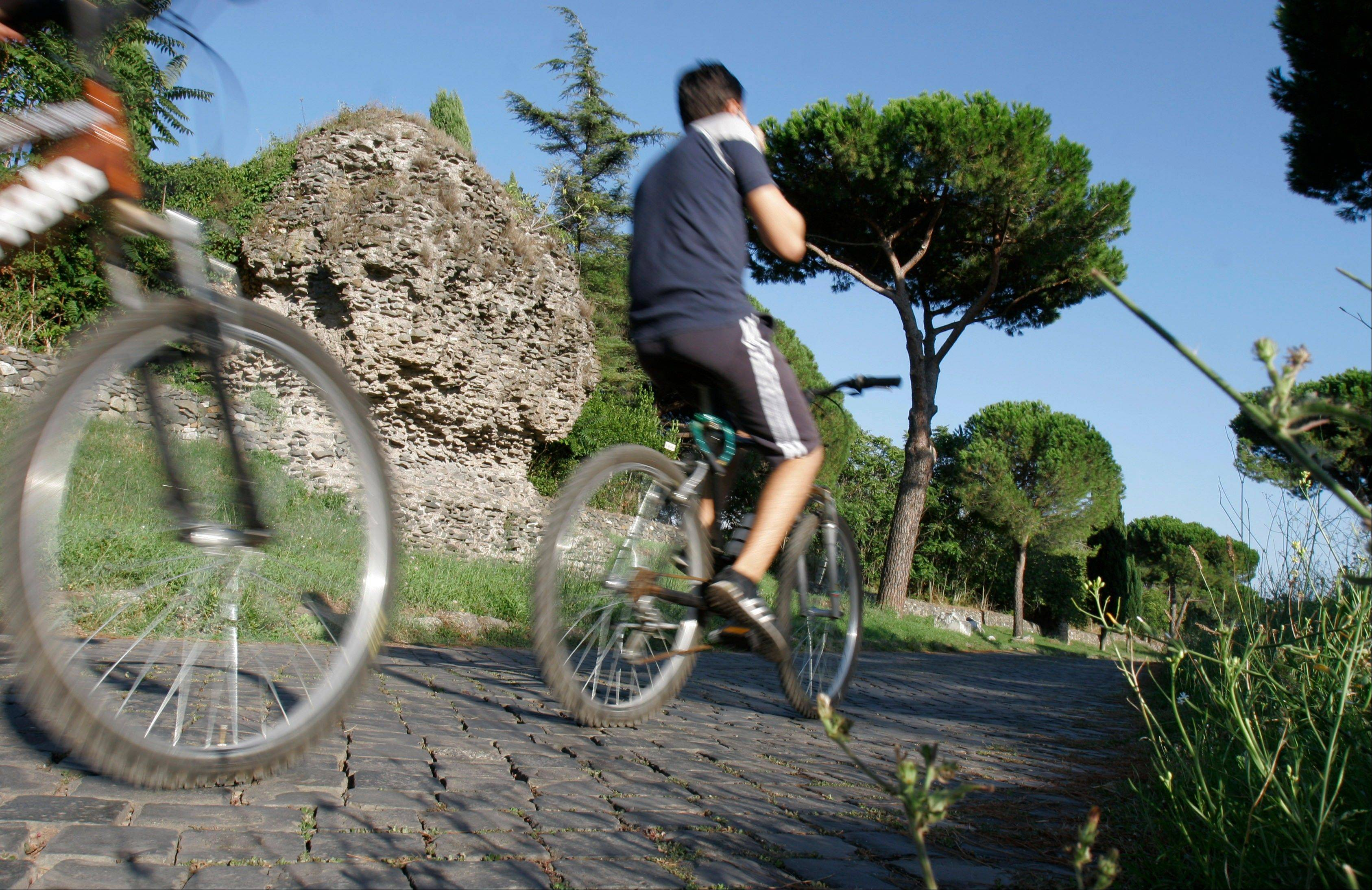 People cycle past ruins along the Appia Antica, the ancient Roman Appian Way, in Rome. The Ancient Appian Way was built in the fourth century B.C. by the censor Appius Claudius as a road to connect Rome with southern Italy.