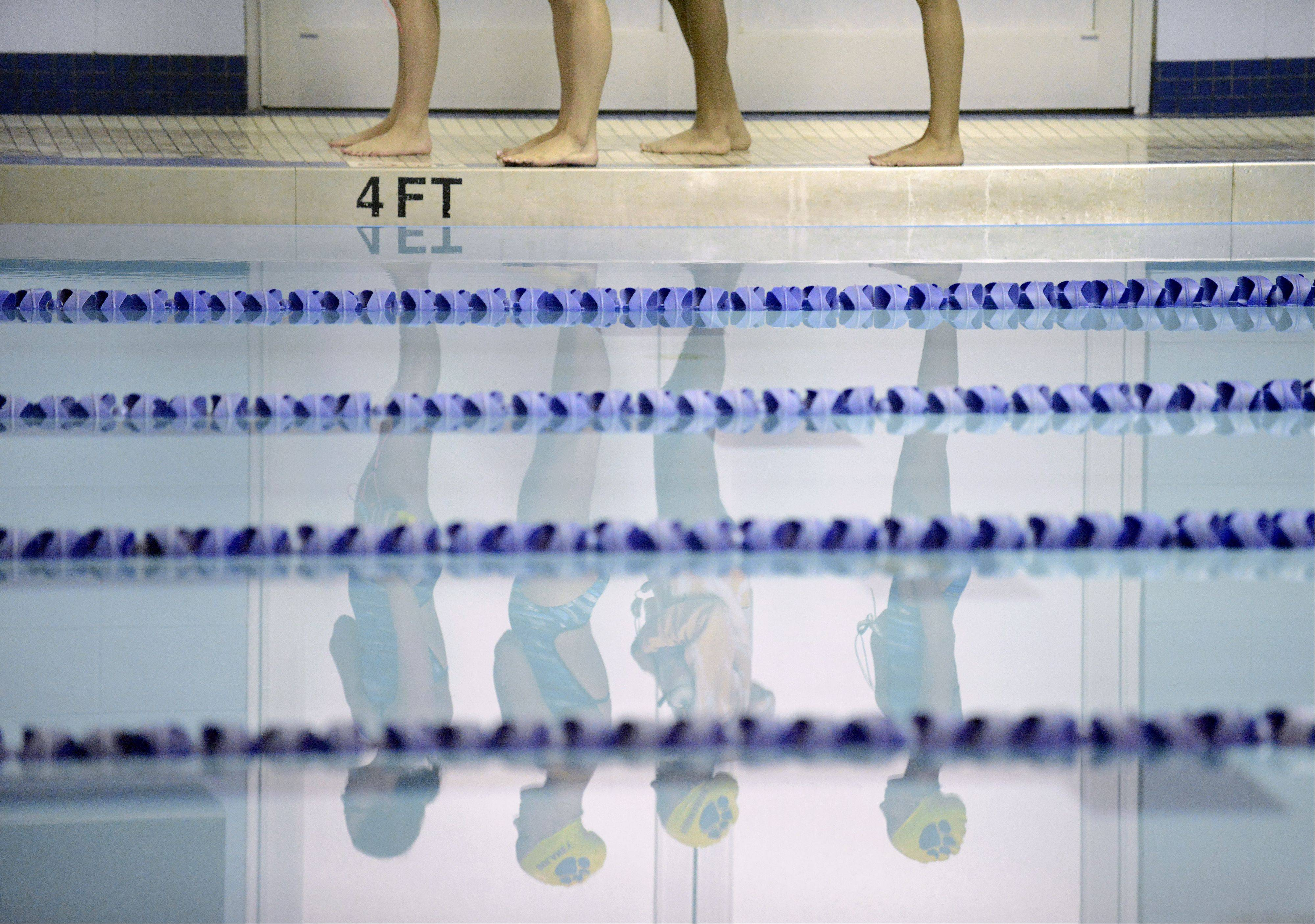 As I stood with my hand on my heart listening to the National Anthem play at a Rosary girls swimming invitational in September, the reflections of four swimmers in the still water caught my eye. Then I saw the 4FT sign on the edge of the pool, realized there were four sets of feet there and I couldn't resist taking a photo. The com