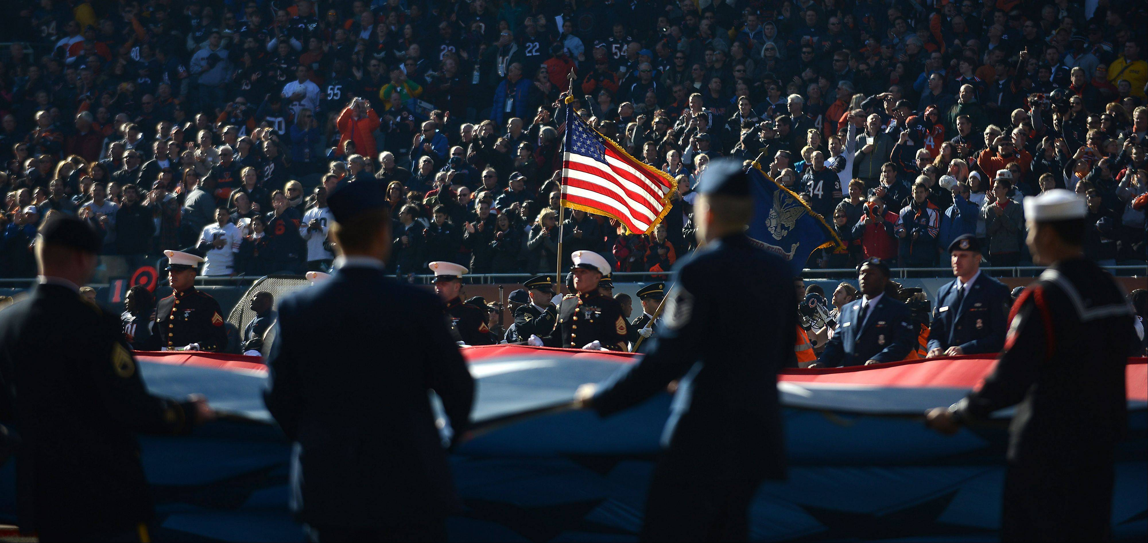 American servicemen and women hold a large American flag during pregame ceremonies before Sunday's game in Chicago.