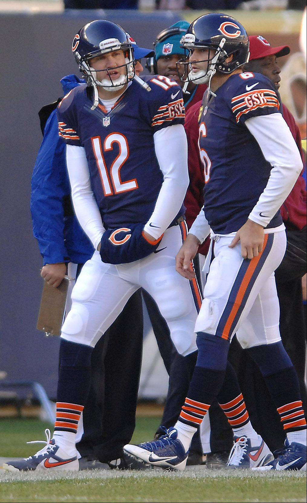 Chicago Bears quarterbacks Josh McCown (12) Jay Cutler (6) confer on the sideline after Cutler comes off the field during the third quarter during Sunday's game in Chicago.