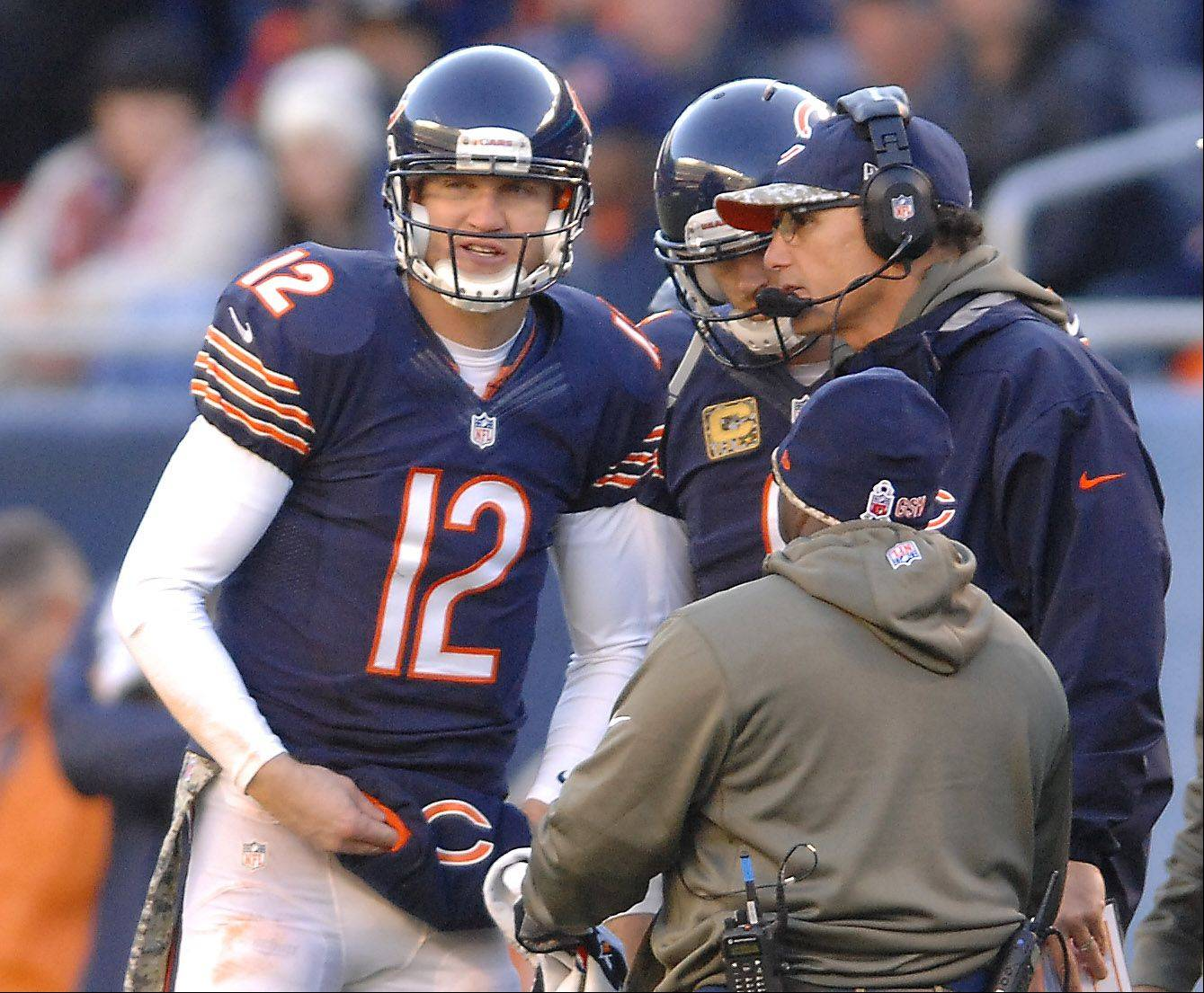 Chicago Bears quarterbacks Josh McCown (12) talks with an injured Jay Cutler and head coach Marc Trestman on the Bears final drive during Sunday's game in Chicago.