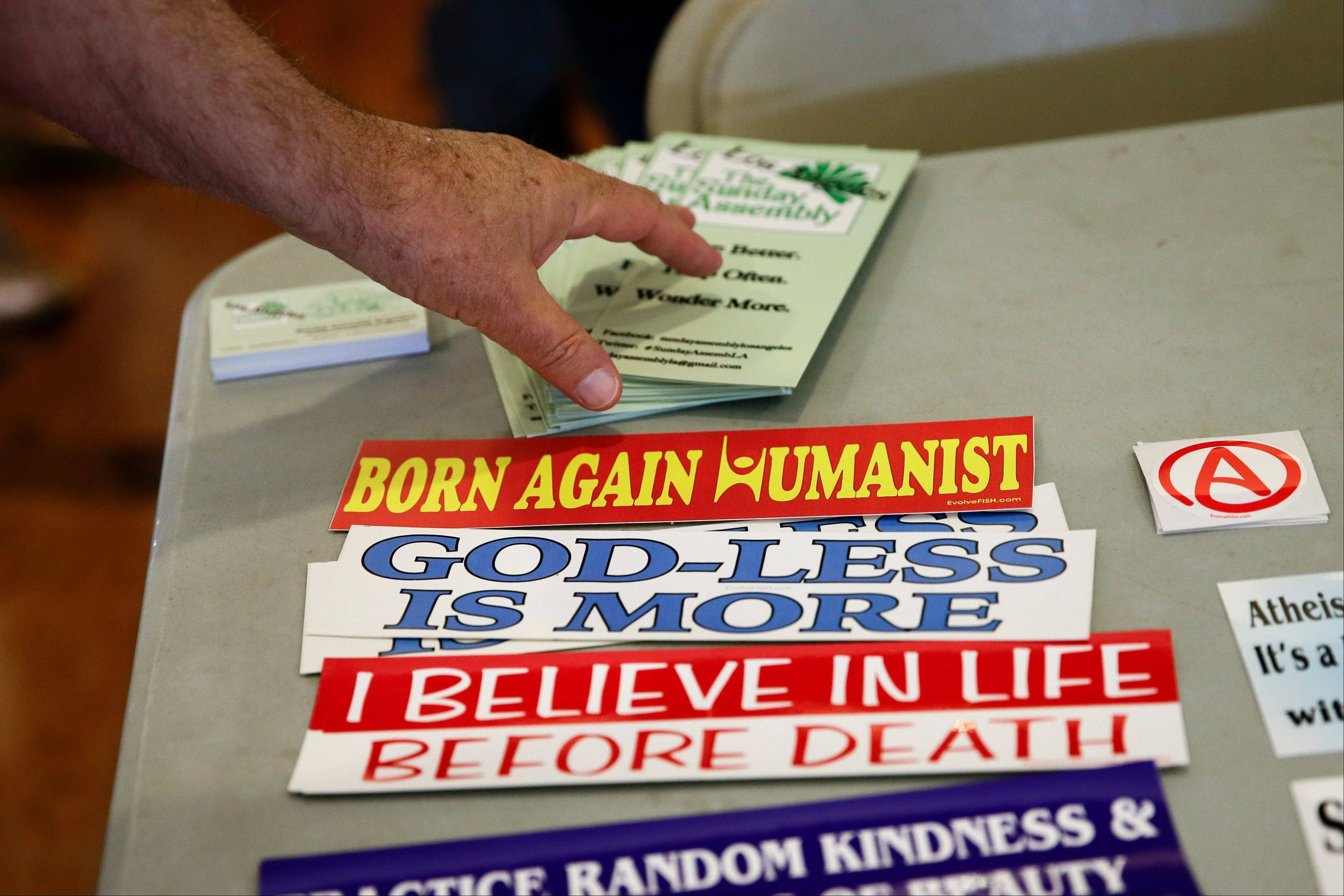 An attendee grabs a brochure at the Sunday Assembly, a godless congregation founded by two British comedians, on Sunday in Los Angeles. A new mega-church movement is generating buzz from London to Los Angeles, but this time it's a belief in non-belief that's drawing crowds on Sunday mornings.