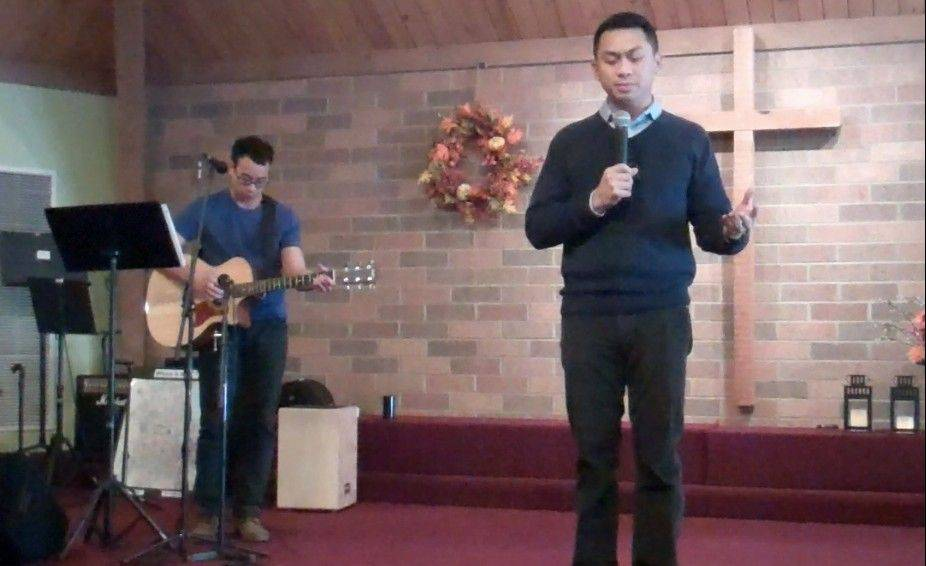 The Rev. Jay Catanus, right, lead pastor at Northwest Filipino Baptist Church in Elk Grove Village, prays while Justin DePaz accompanies him on guitar. Many church members are still waiting to hear from family members in the Philippines who may have been impacted by the deadly Typhoon Haiyan.