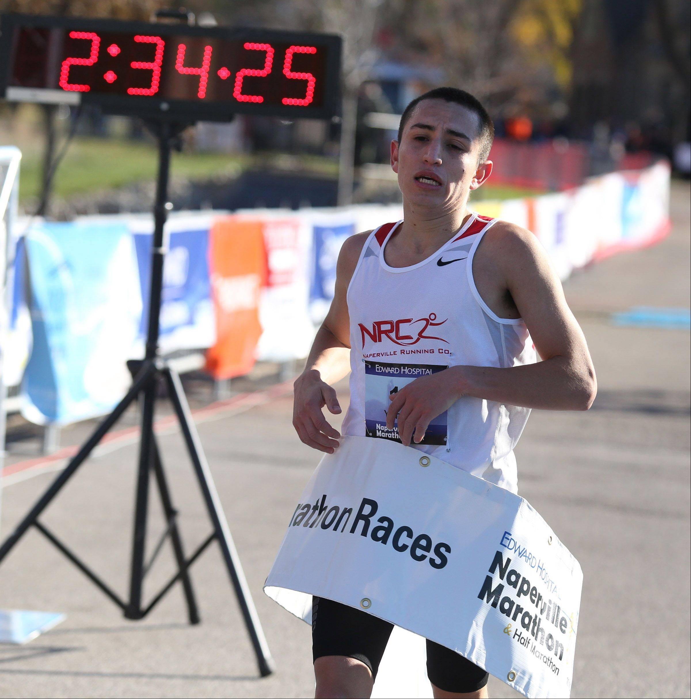Yonatan Mascote of Naperville crossing the finish line first in the Edward Hospital Naperville Marathon on Sunday, November 10, 2013.
