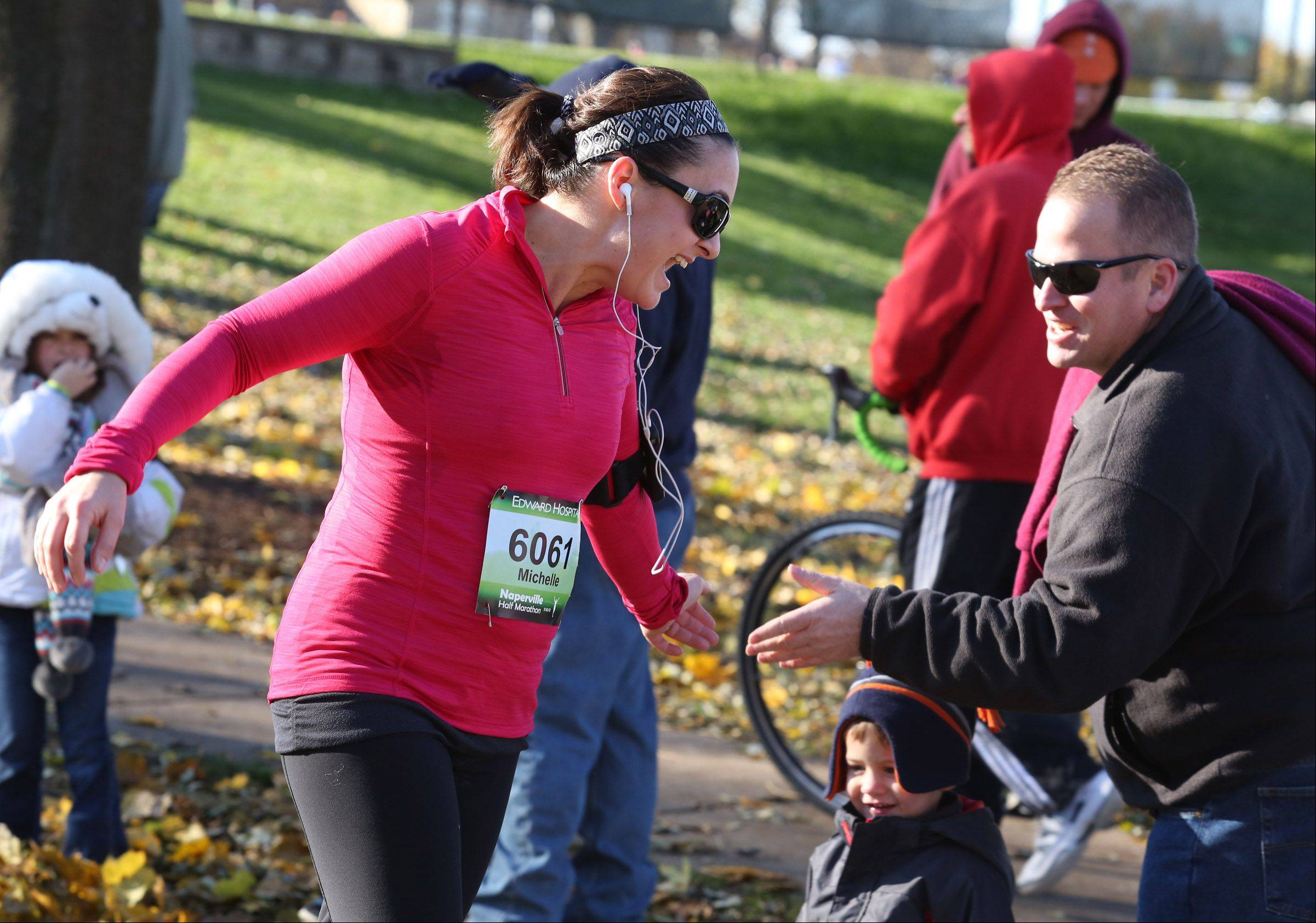 Michelle Huber of Elmhurst gets a hand from her husband, Bill, just before crossing the finish line in the Edward Hospital Naperville half marathon on Sunday, November 10, 2013.