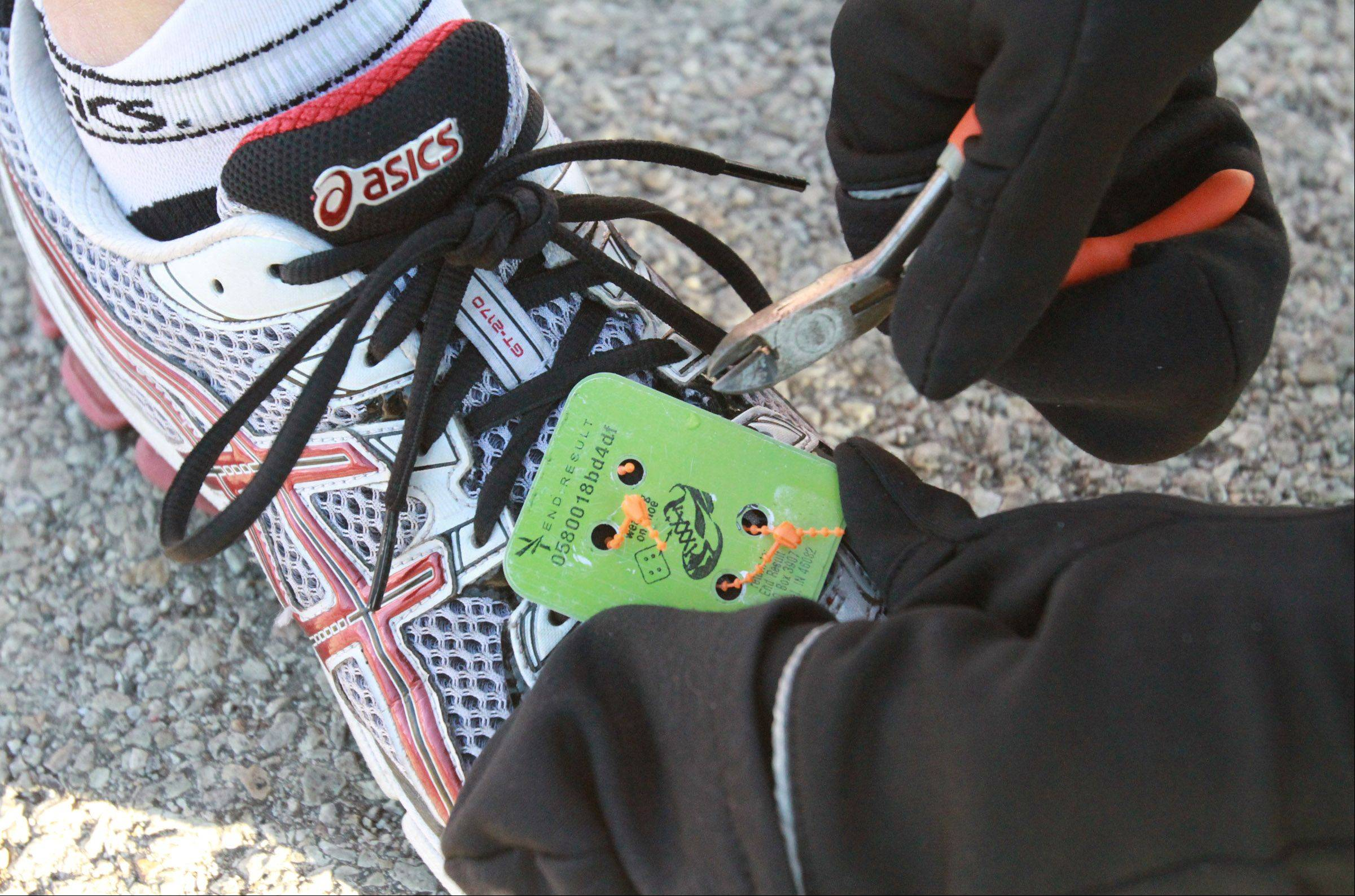 A runners tag is removed after completing the Edward Hospital Naperville half marathon on Sunday, November 10, 2013.