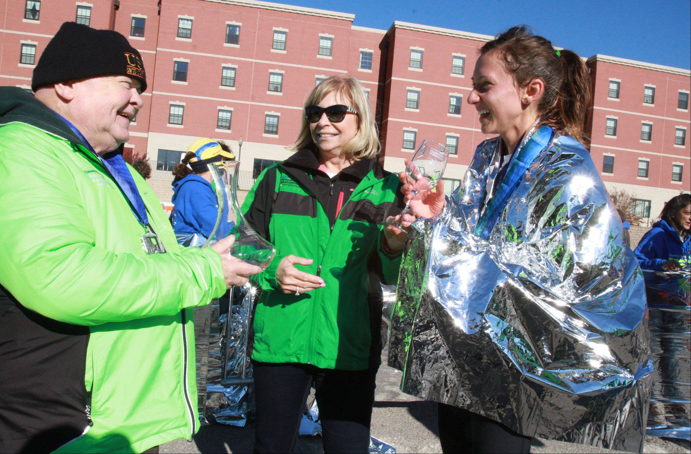 Amanda Mirochna of Naperville, the first women to cross the finish line, receives two awards from the Mayor of Naperville George Prade and Pam Davis, president of Naperville Edward Hospital, at the Edward Hospital Naperville Marathon on Sunday, November 10, 2013.