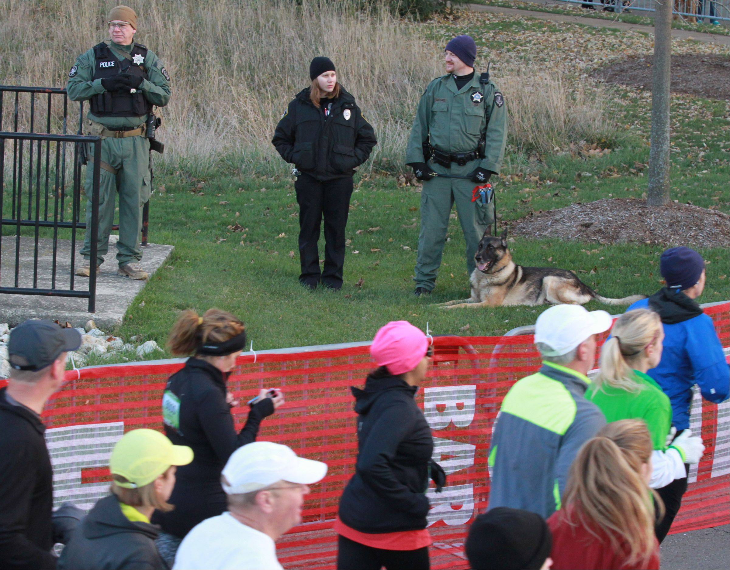 A police K-9 officer watches runners near the start of the inaugural Edward Hospital Naperville Marathon on Sunday, November 10, 2013.