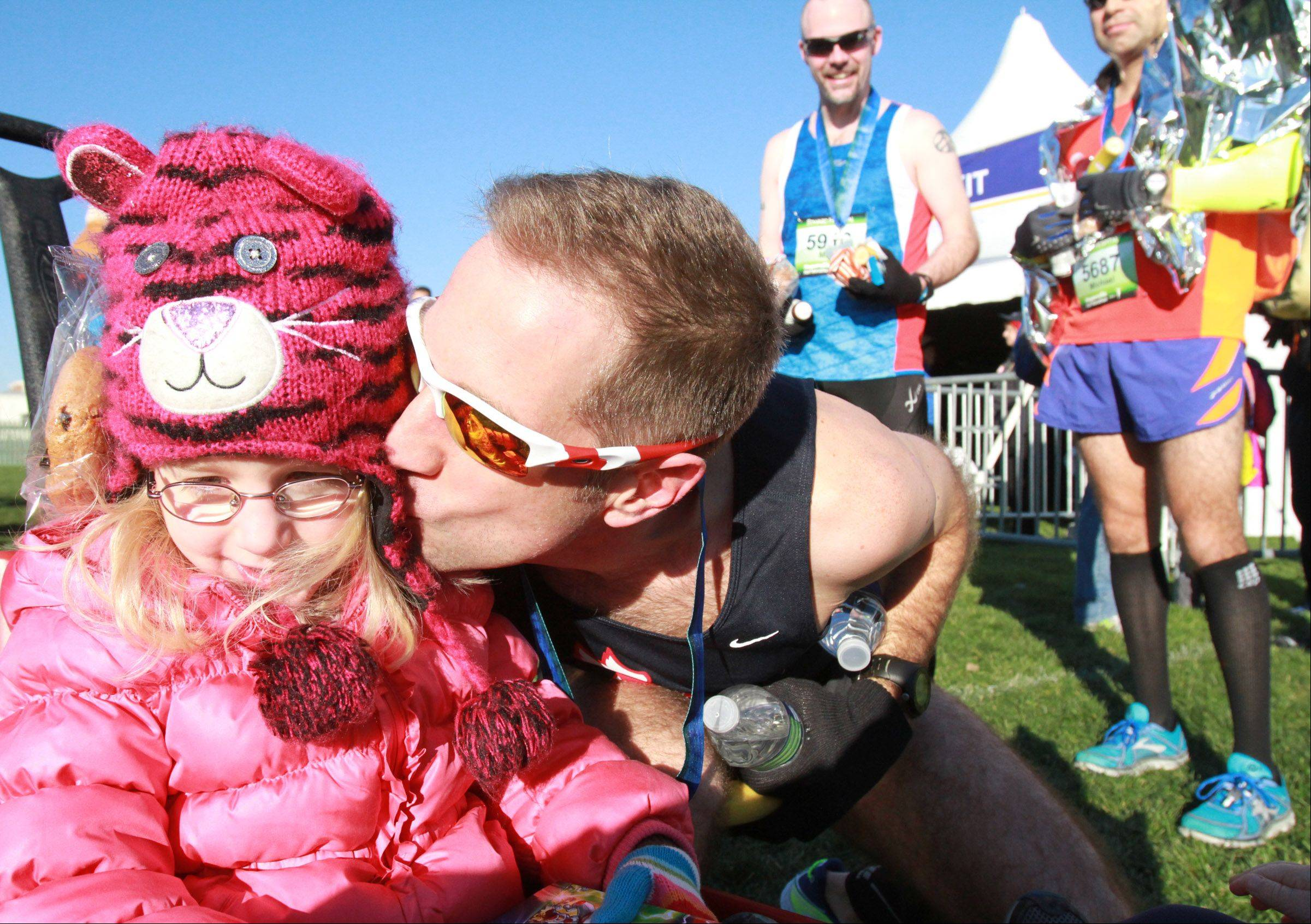 Matt Longino of Downers Grove kisses his four-year-old daughter, Brooke, after Matt competed the Edward Hospital Naperville half marathon on Sunday, November 10, 2013.