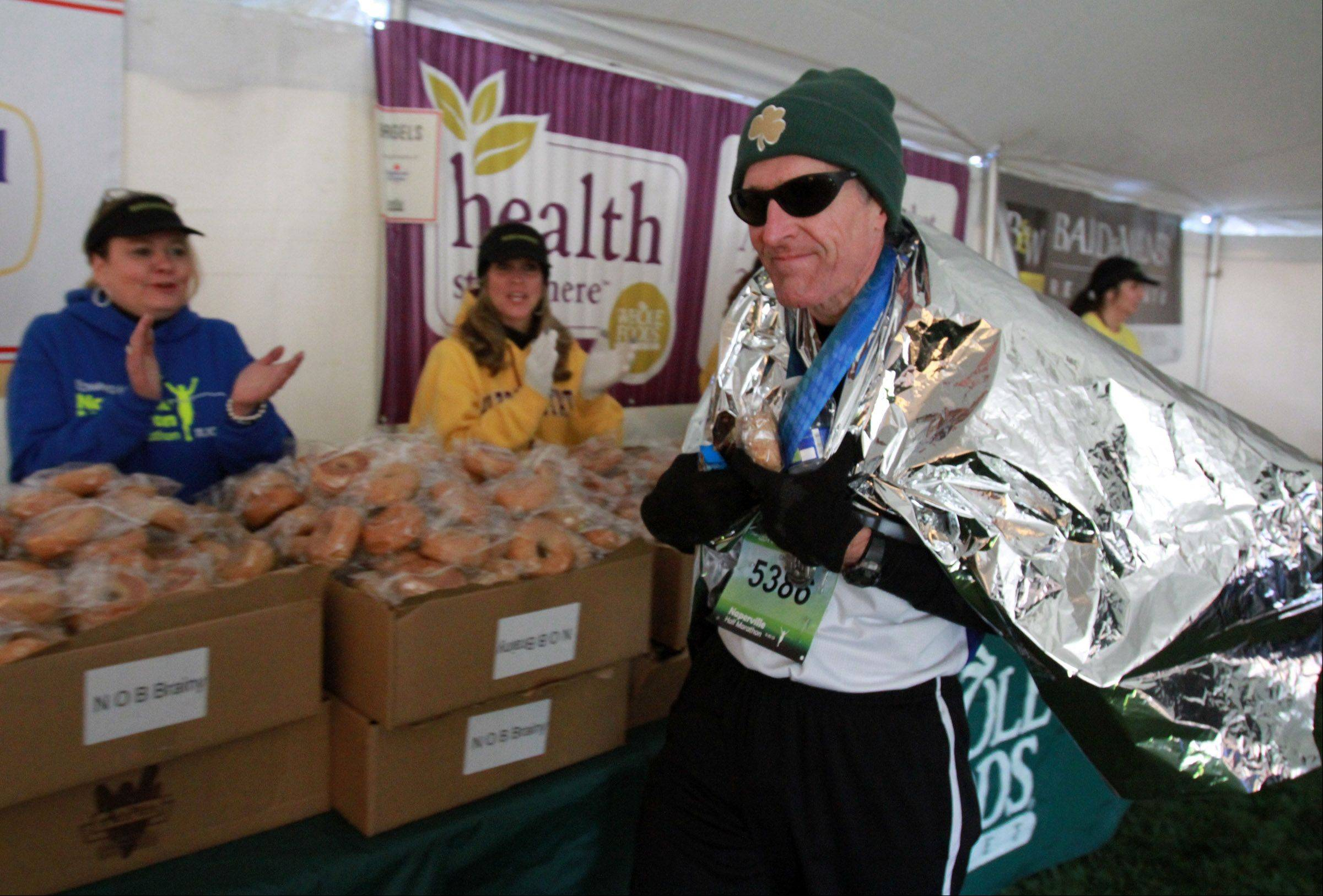 James Owens of Bradford receives a hand from volunteers in the food tent after completing the Edward Hospital half Marathon on Sunday, November 10, 2013.
